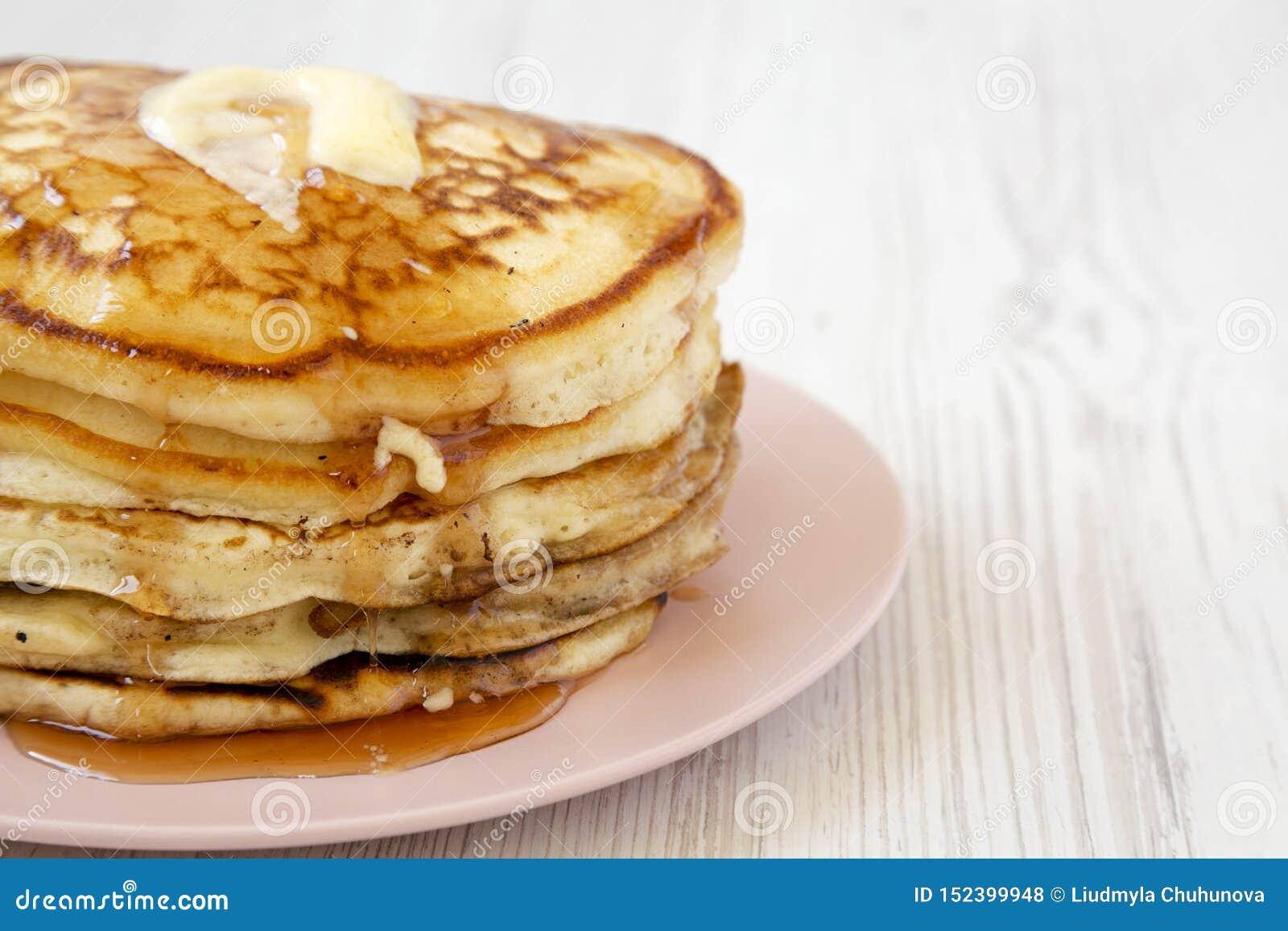 Hemlagade pannkakor med smör- och lönnsirap på en rosa platta, sidosikt kopiera avst?nd