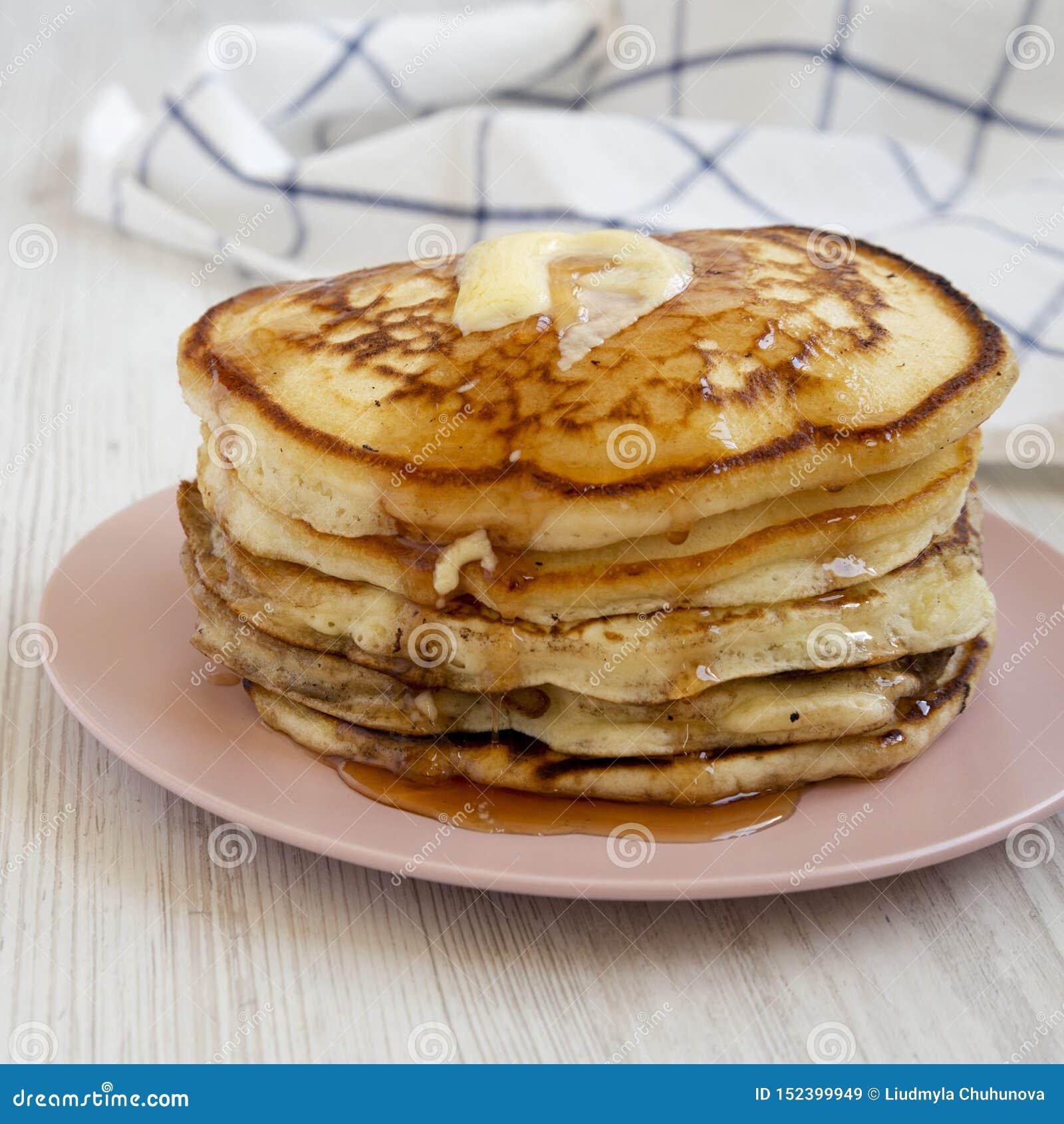 Hemlagade pannkakor med smör- och lönnsirap på en rosa platta, sidosikt N?rbild