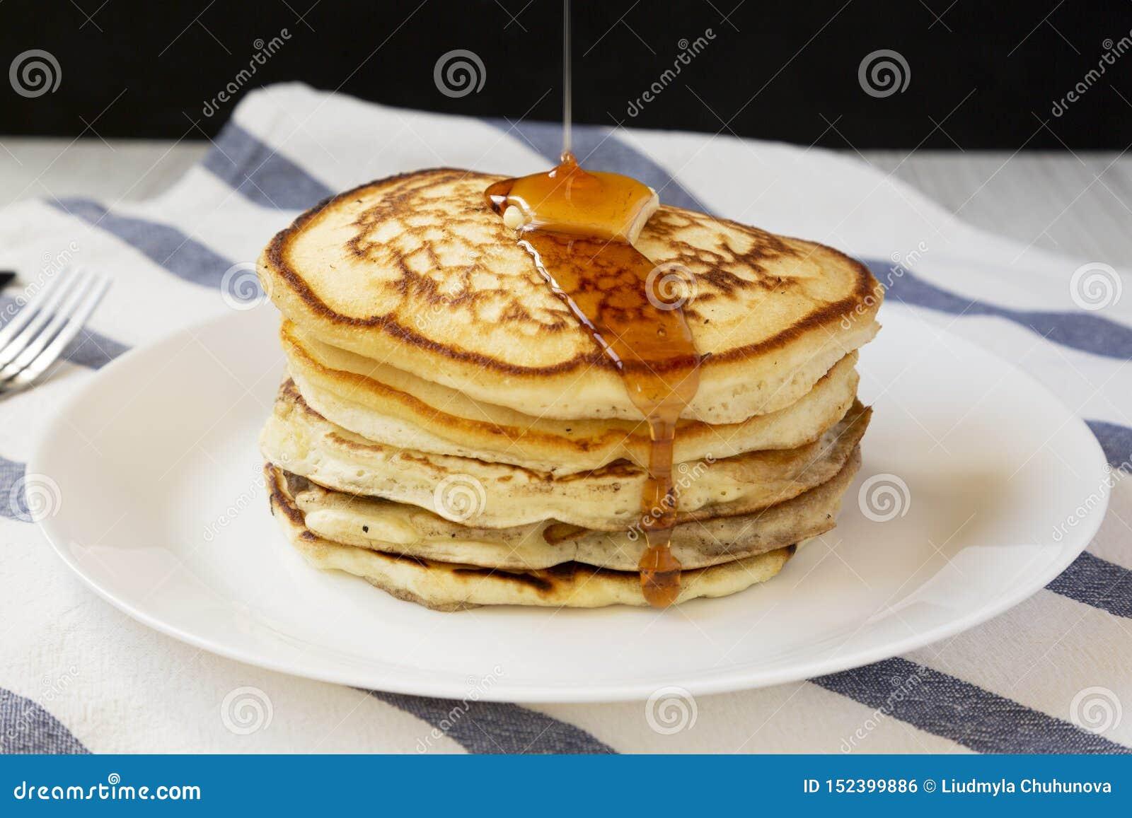 Hemlagade pannkakor med smör- och lönnsirap på en vit platta, sidosikt closeup