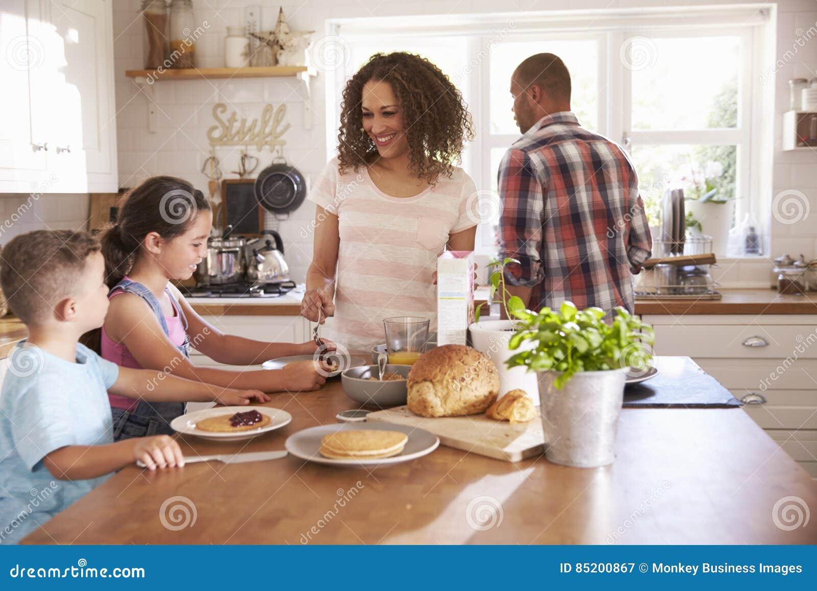Hemmastadd ätafrukost för familj i kök tillsammans