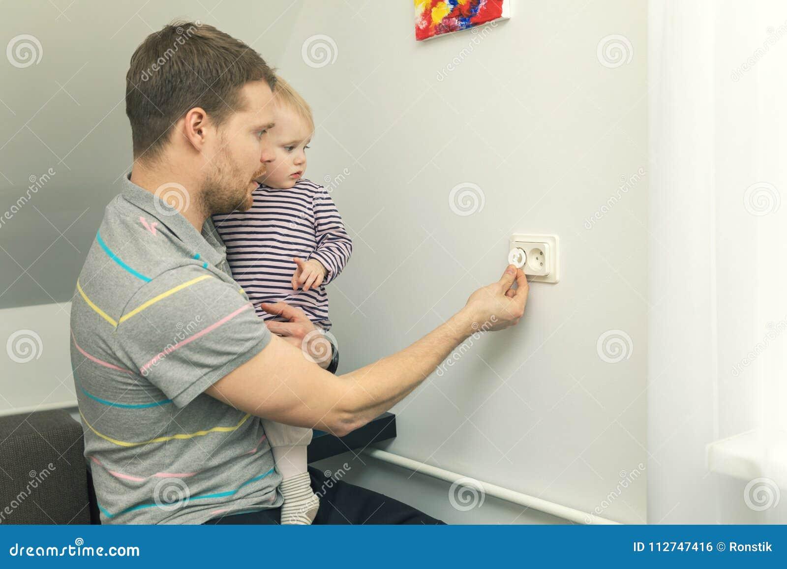 Hemmastadd barnsäkerhet fadern skyddar ungen från elektrisk skada