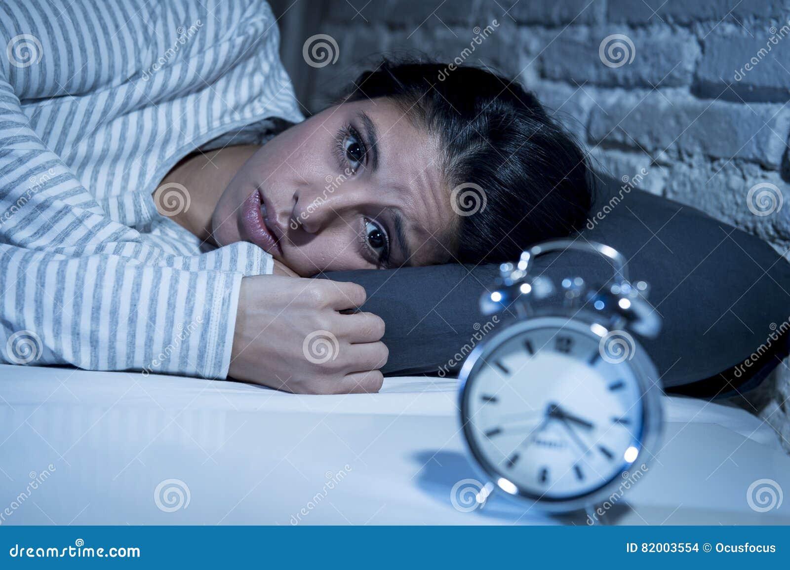 Hemmastatt sovrum för latinamerikansk kvinna som sent ligger i säng på natten som försöker att sova lidandesömnlöshet