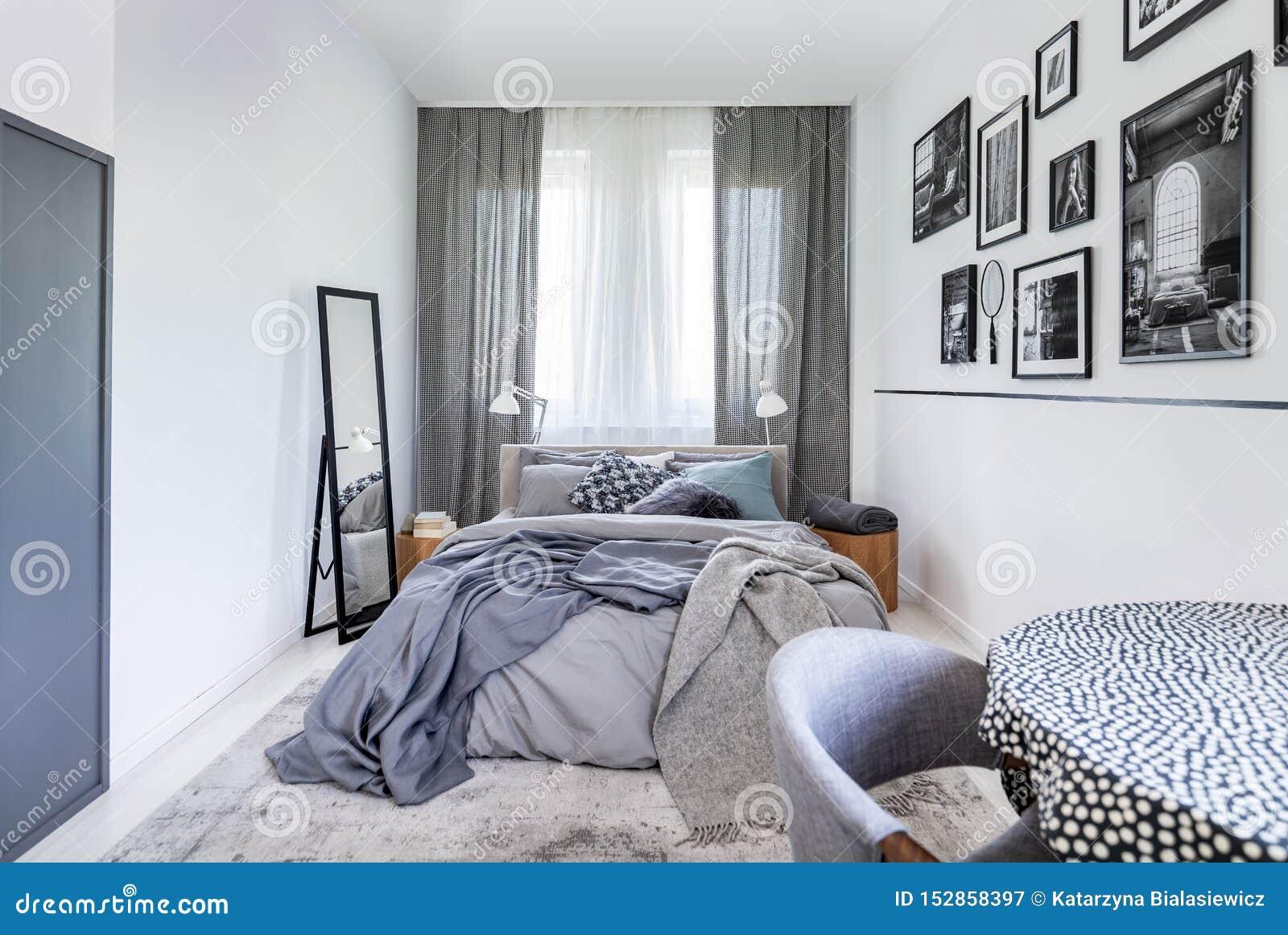 Hemtrevliga kuddar på bekväm stor konungformatsäng i det ljusa sovrummet som är inre i elegant lägenhet