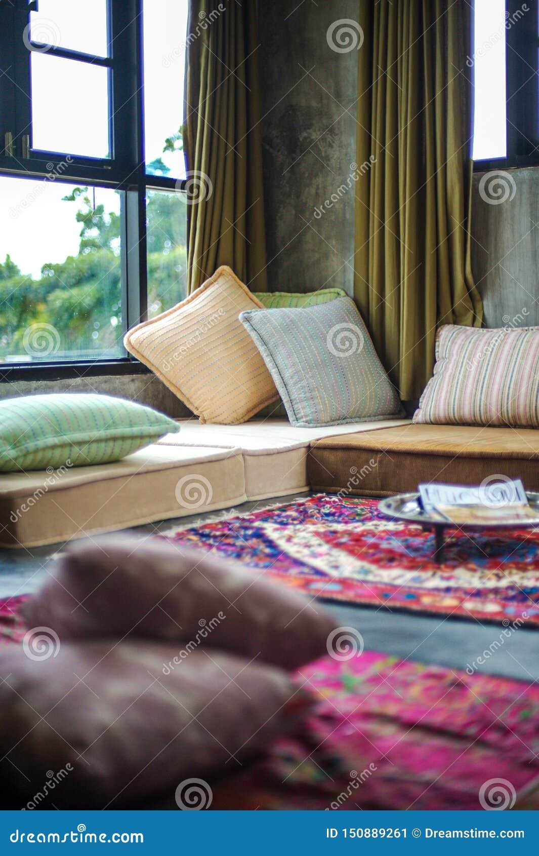 Hemtrevligt ställe med kuddar nära fönstren, ett bra ställe för läseböcker