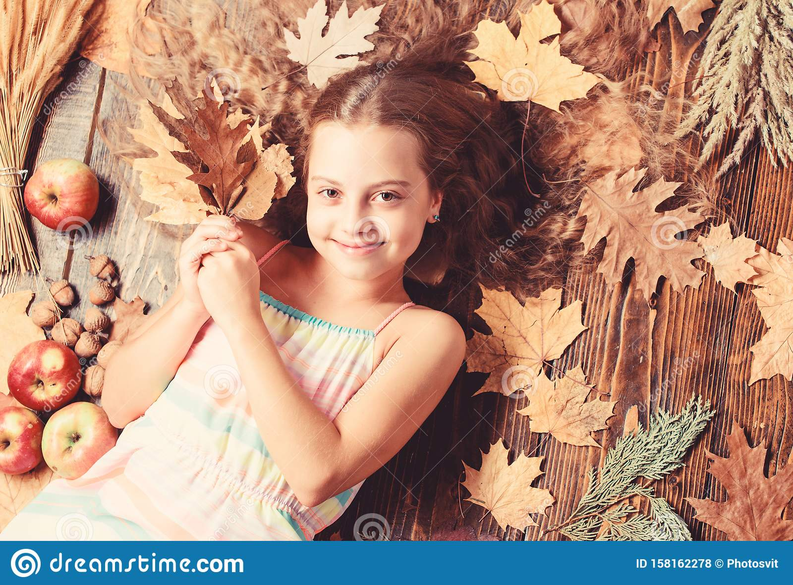Her hair at its best. Little girl with wavy hairstyle on fall background. Small beauty model with fall look. Hair salon