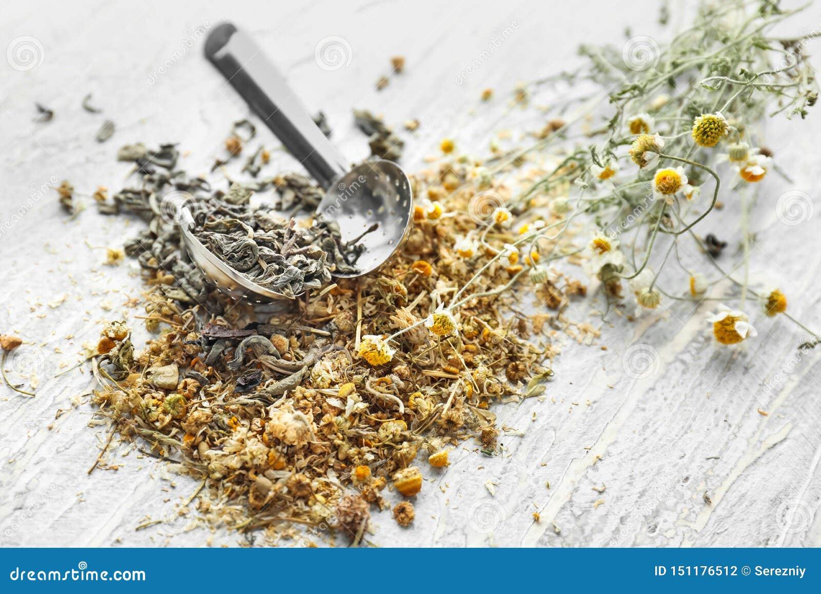 Herbaciany durszlak z wysuszonym chamomile kwitnie na drewnianym stole