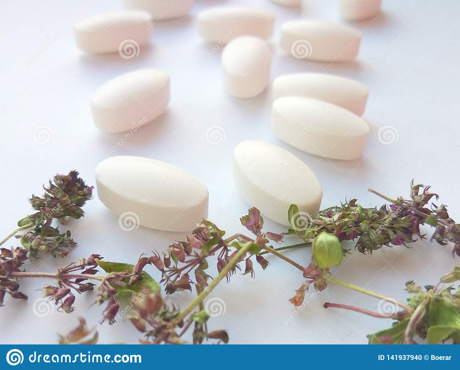 Herbal medicine pills with dry natural herbs on white background. Concept of herbal medicine and dietary supplements