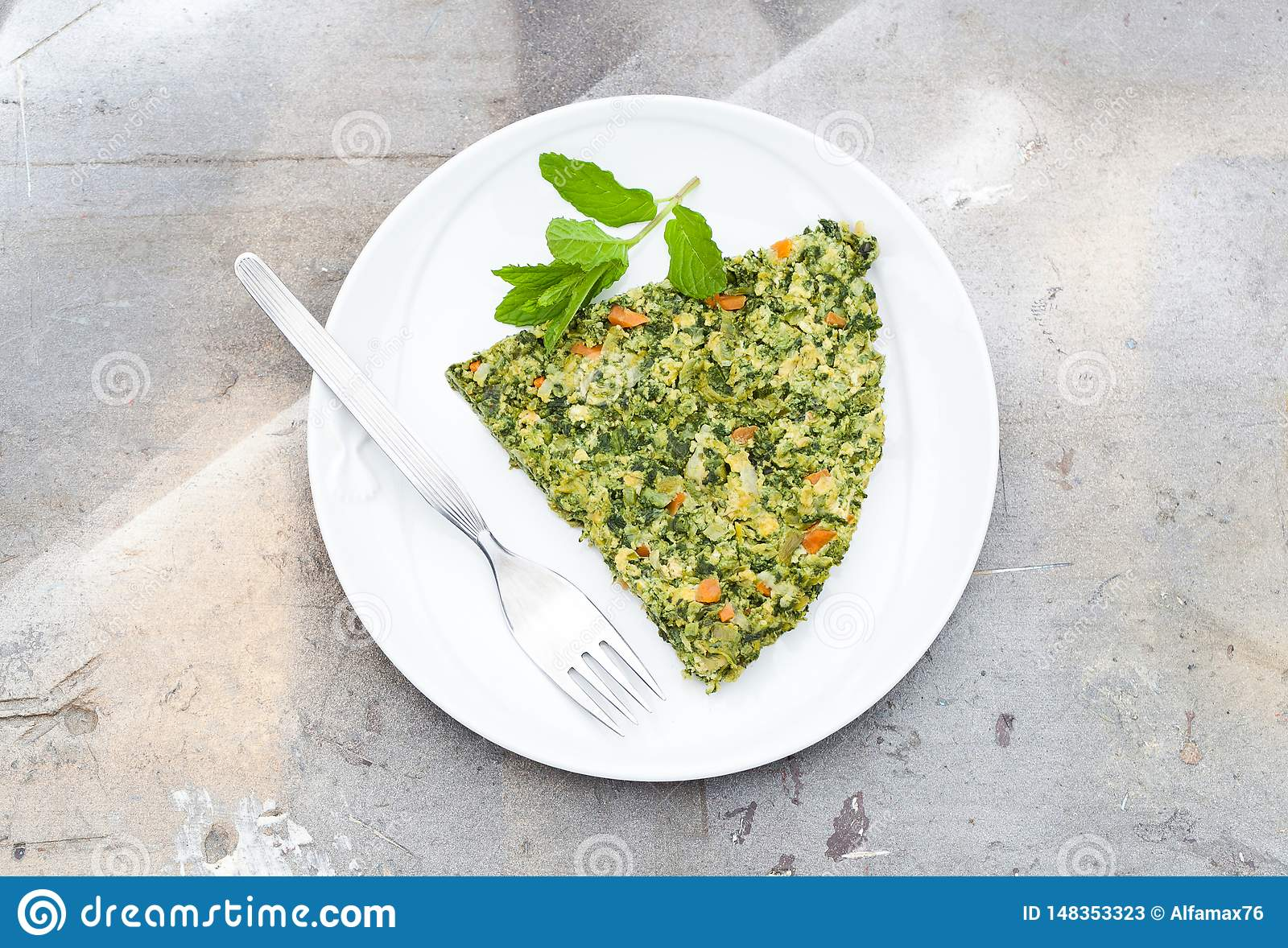 Omelet made of eggs, green asparagus, pea, carrot,cheese, parsley and mint, wood background with natural light