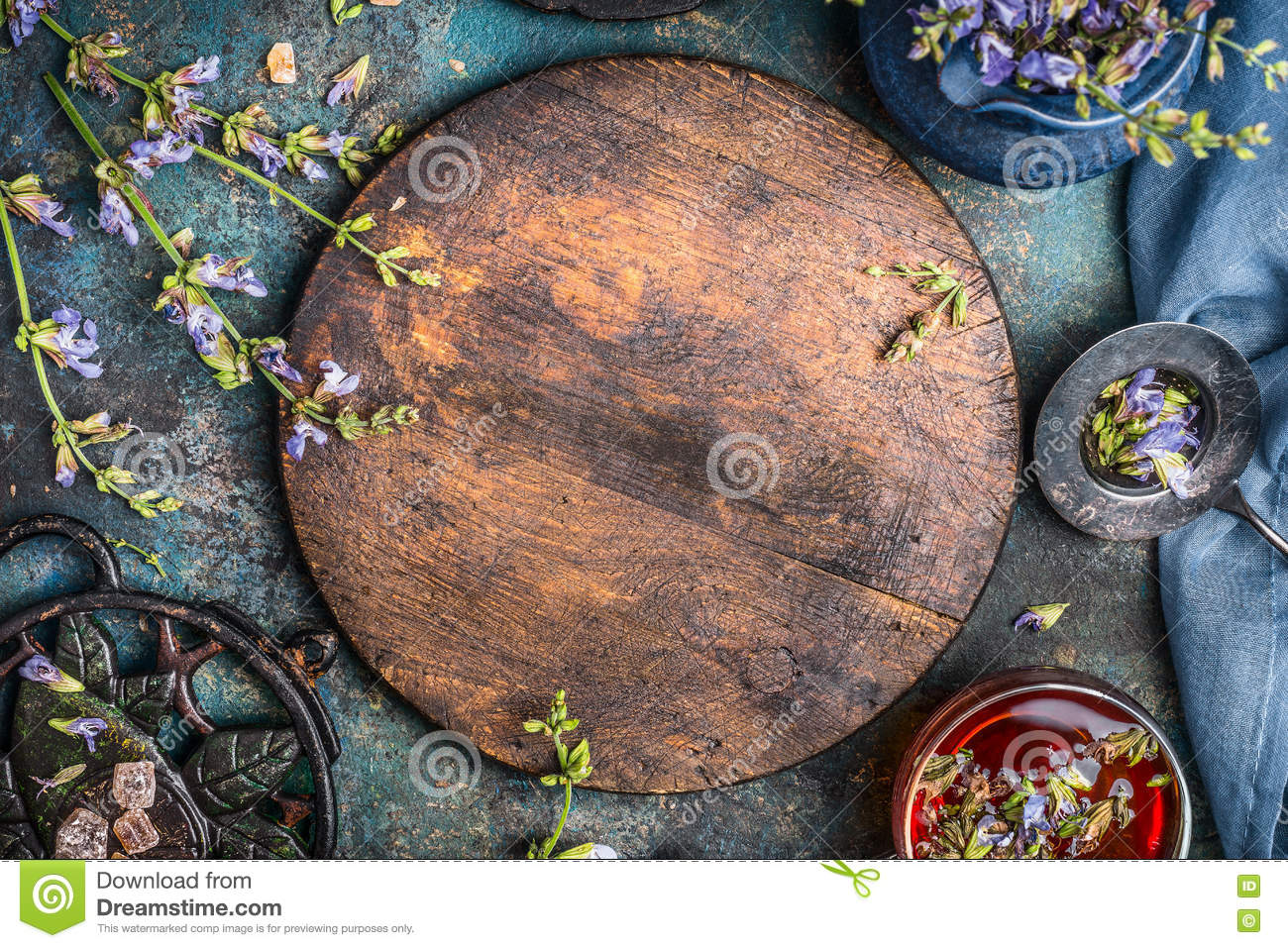 Herbal tea background with round wooden board, cup of tea and various flowers and healing herbs on dark background, top view