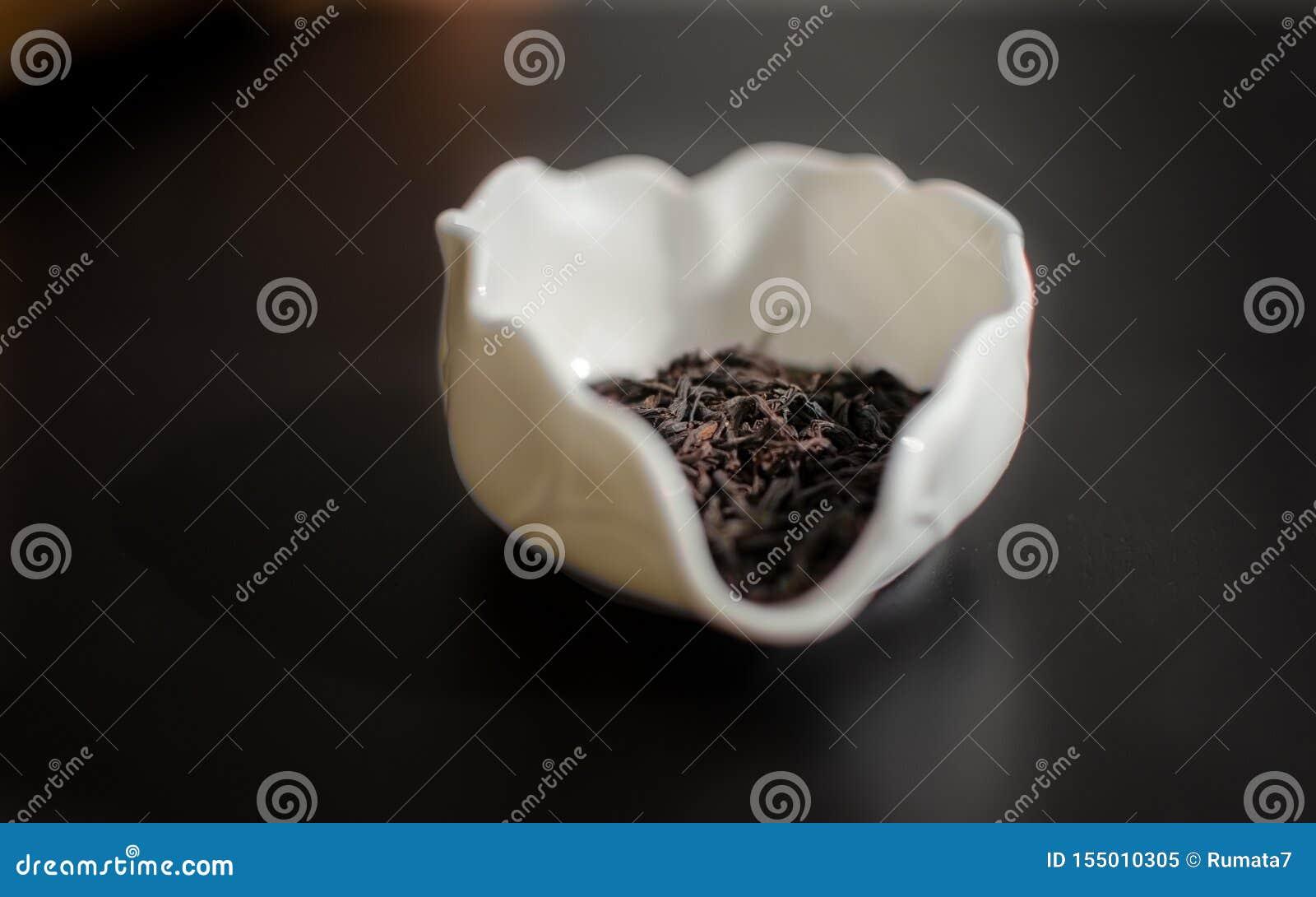 Herbata staczająca się opuszcza w «Chahe «specjalnego puchar - przedstawiać herbacianych liście