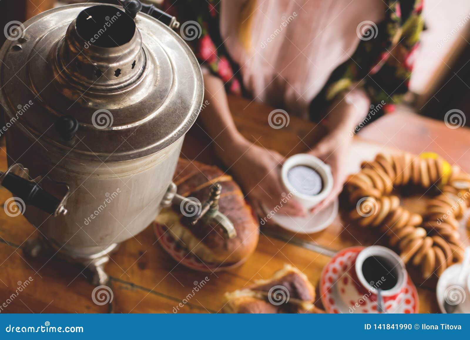 Herbata, tradycyjni rosjanów naczynia i fundy, samowar na stole ręki kobieta w krajowej chustce trzymamy filiżankę