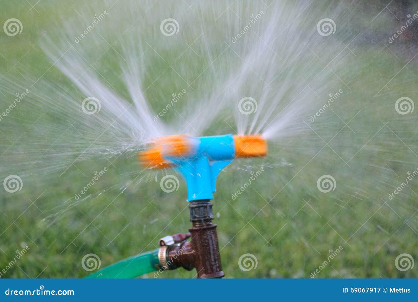Herbe de arrosage d 39 arroseuse bleue et orange pelouse de arrosage de syst - Systeme irrigation jardin ...