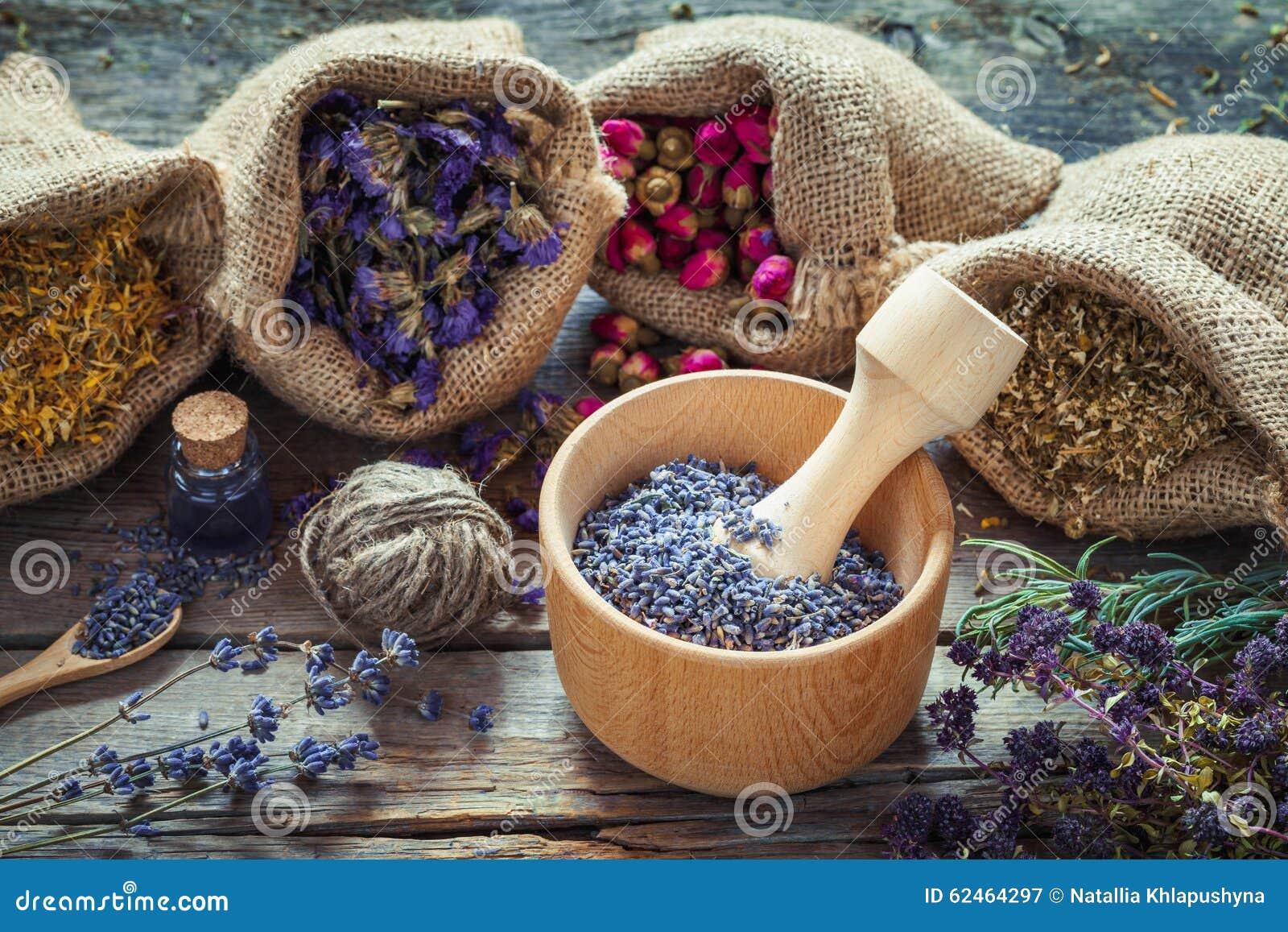 Herbes curatives dans les sacs hessois, mortier en bois avec la lavande sèche