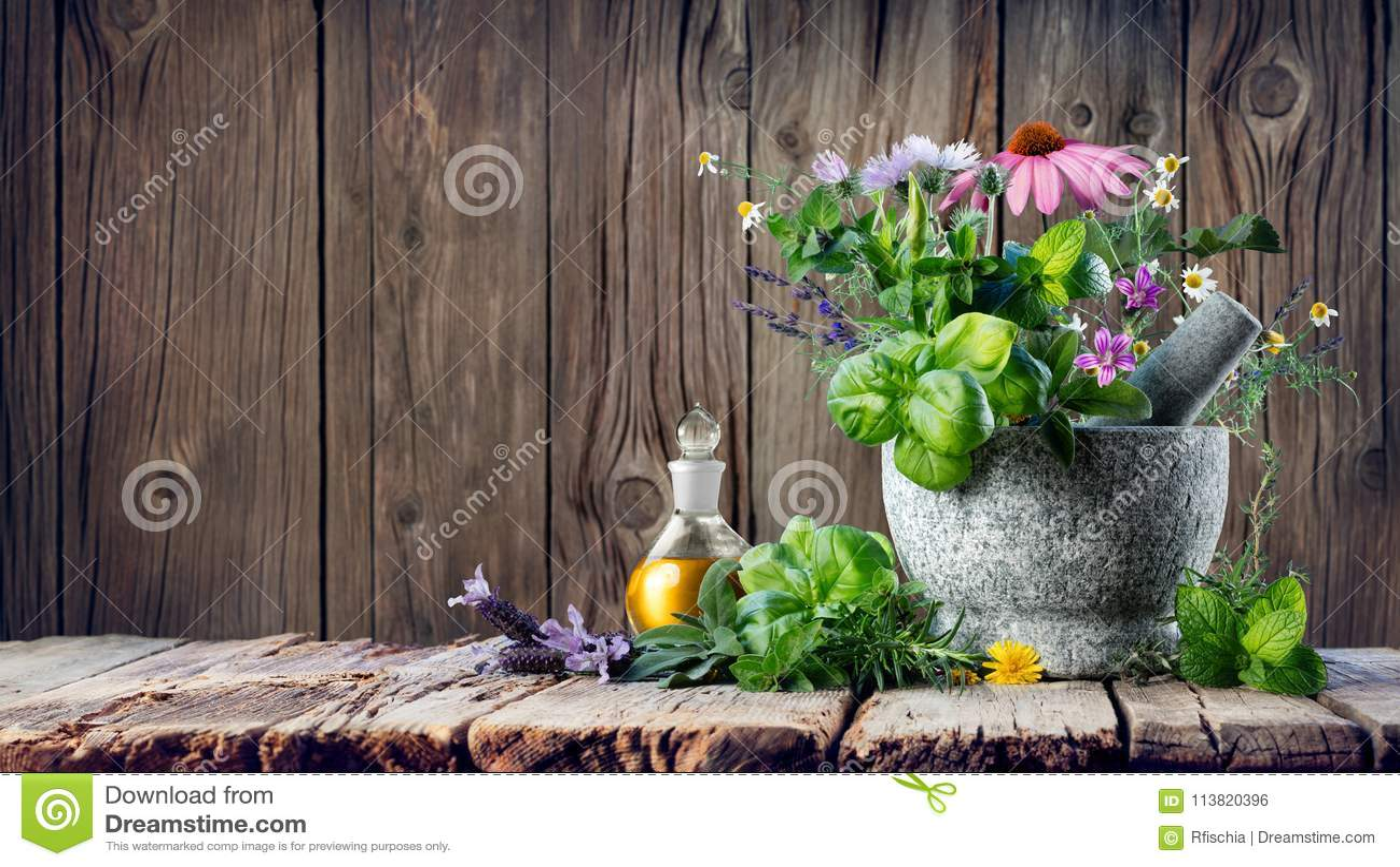 Herbes curatives et huile essentielle dans la bouteille avec le mortier