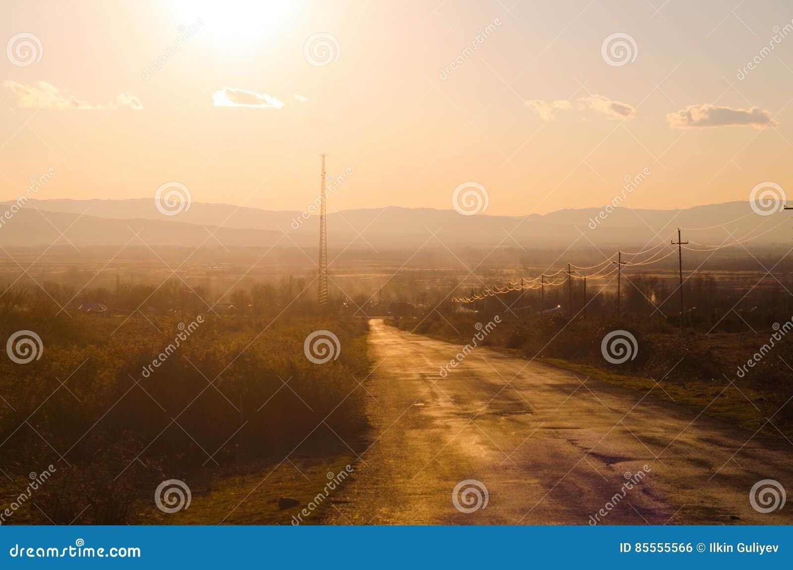 Herbst- oder Winterlandschaft mit Straße und Bäumen Der Goldlichtstrahlsonnenuntergang Auf einem Hintergrund von Bergen und von H