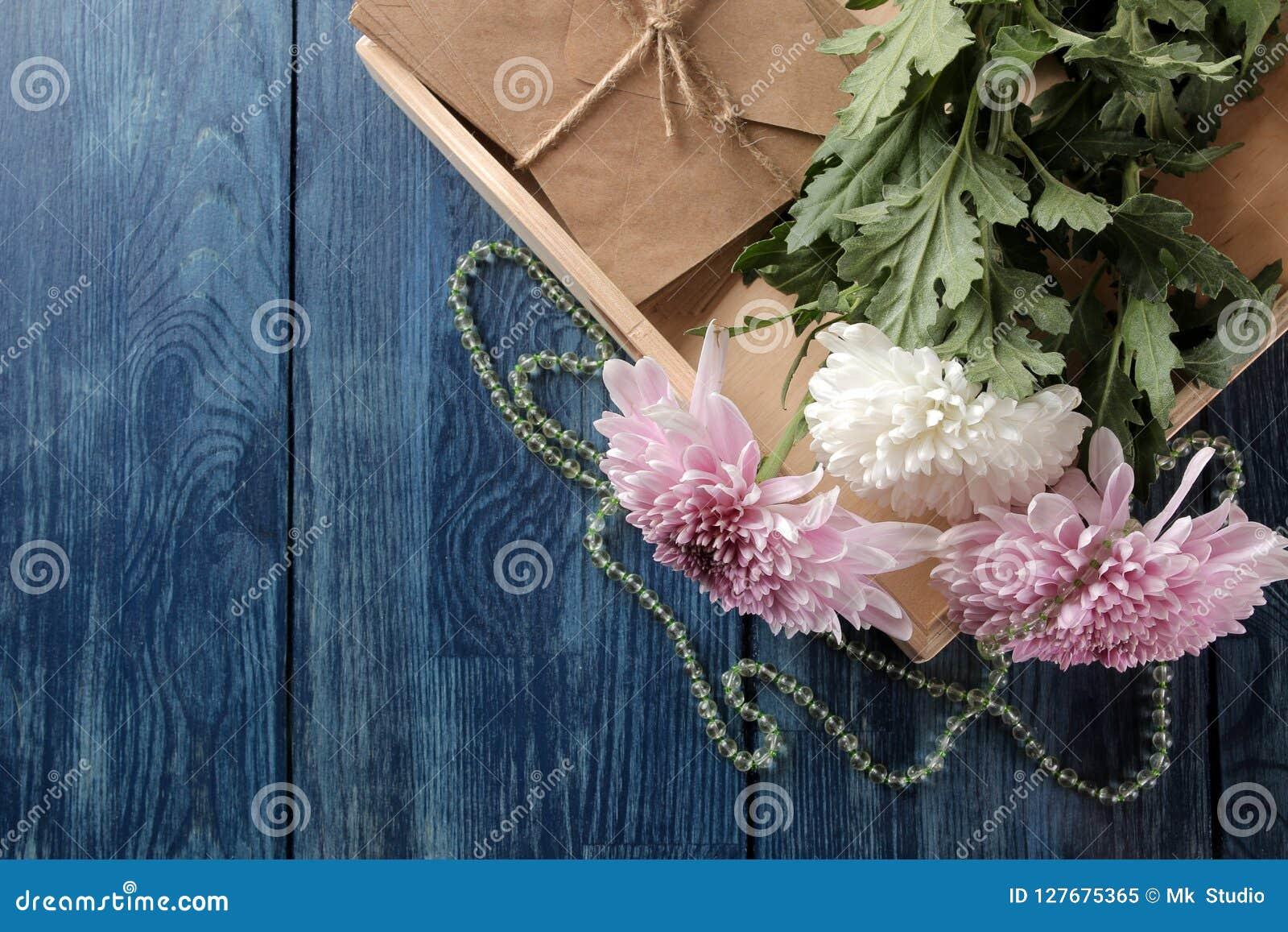 Herbstblumen der Chrysantheme mit Perlen und Buchstaben auf einer dunkelblauen Tabelle mit einem Platz für Aufschrift