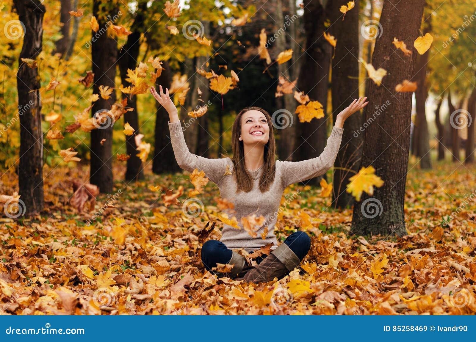 Herbstmädchen, das im Stadtpark spielt Fallfrauenporträt der glücklichen reizenden und schönen jungen Frau im Wald in den Fallfar