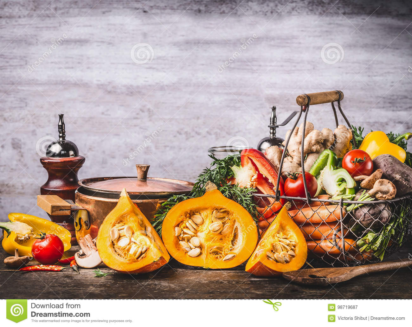 Herbstsaisonlebensmittelstillleben mit Kürbis, Pilze, verschiedenes organisches Erntegemüse und kochen Topf auf rustikalem Küche