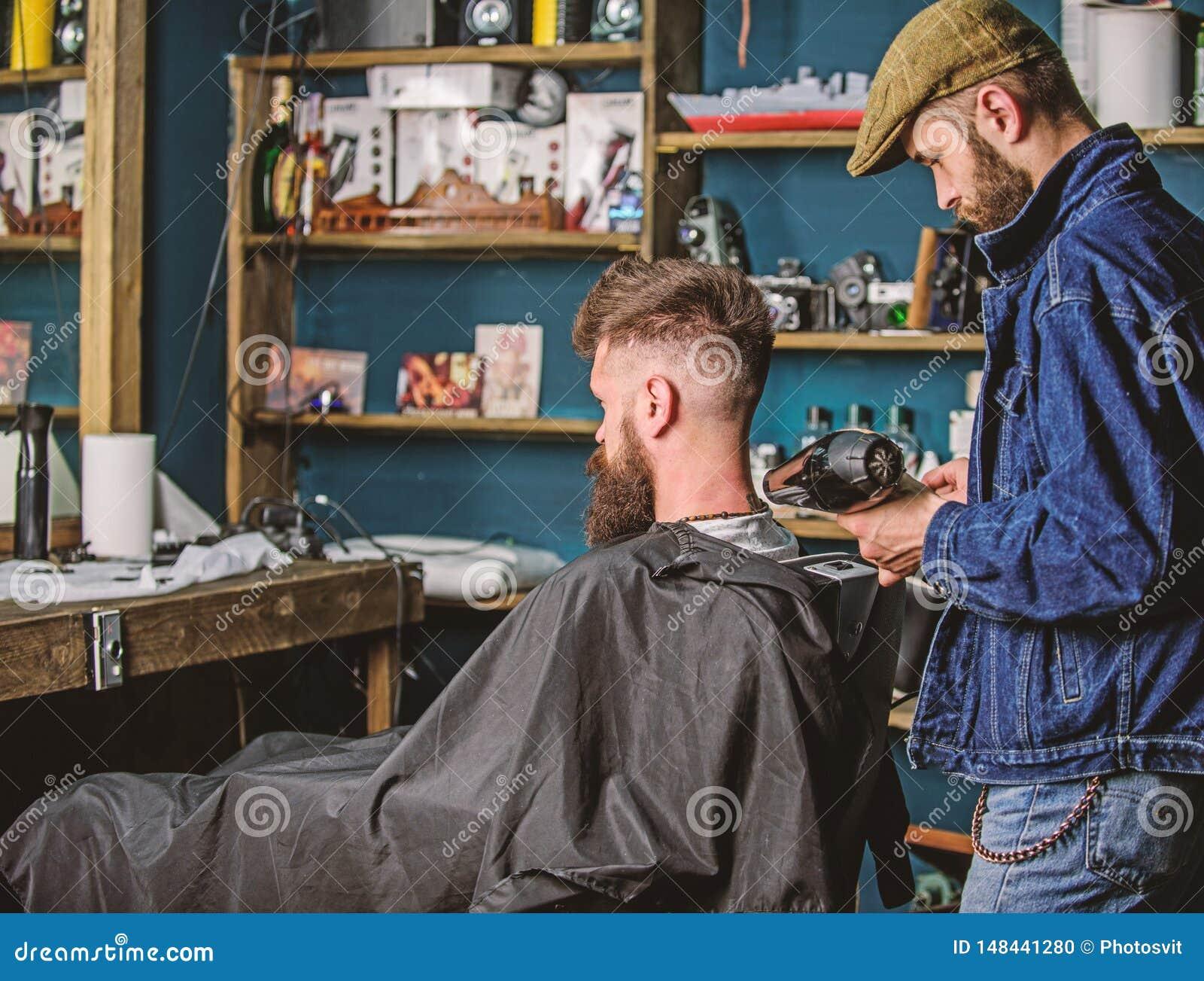 Herenkapperconcept De kapper met hairdryer blaast haar uit kaap weg Hipster gebaard cli?nt geworden kapsel Kapper met