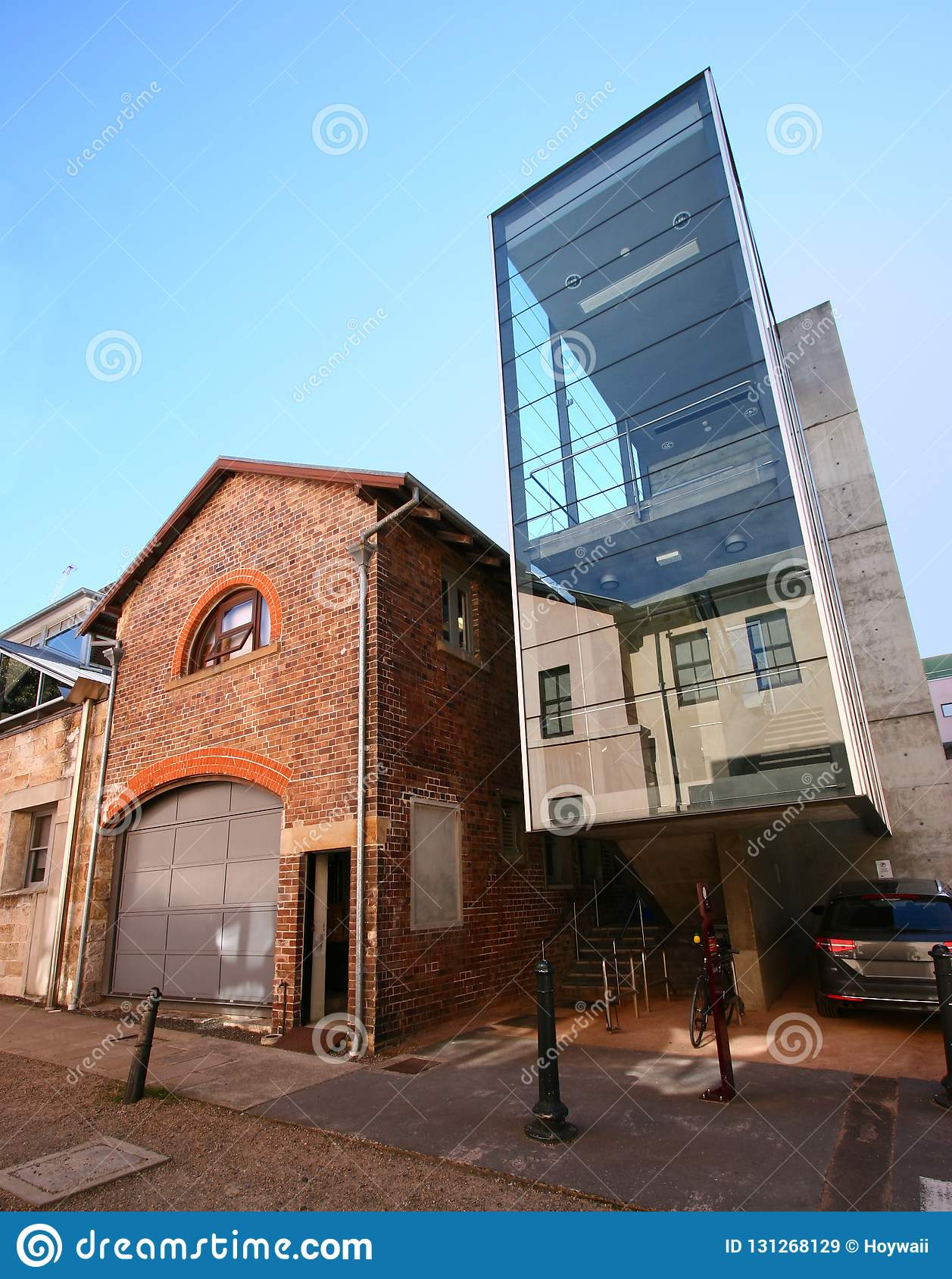 Modern architectural glass stairwell extension added to existing old historic brick building in Sydney Mint in urban downtown CBD