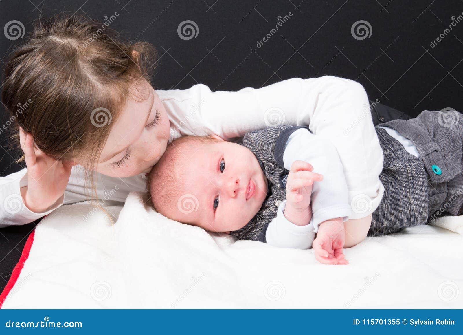 Hermana que besa su niña pequeña del niño del pequeño hermano y bebé recién nacido en el concepto de vida familiar