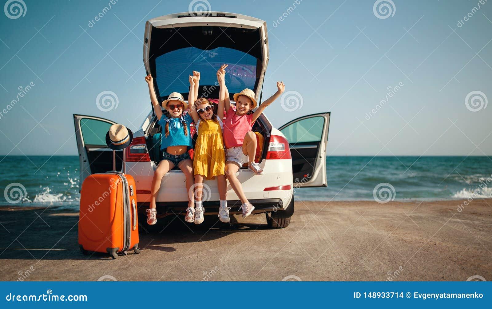 Hermanas felices de los amigos de muchachas de los ni?os en el paseo del coche al viaje del verano