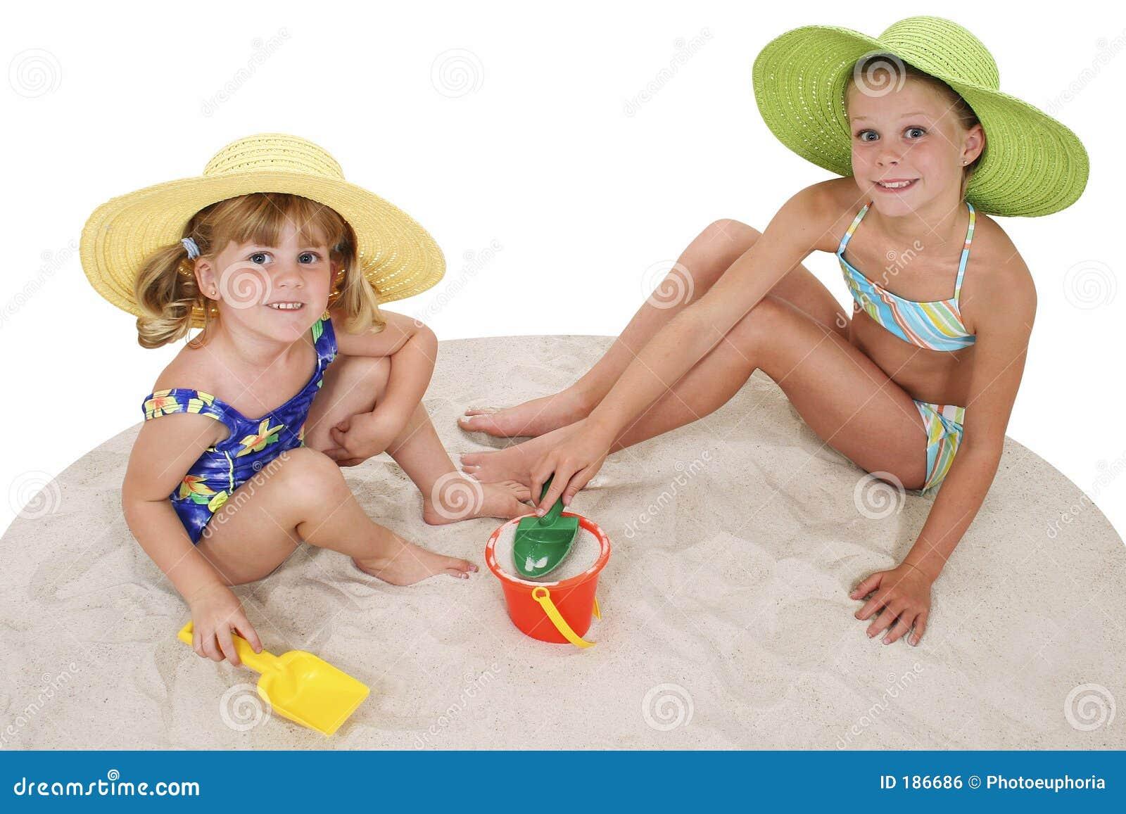 Hermanas hermosas en los sombreros de la playa que juegan en la arena
