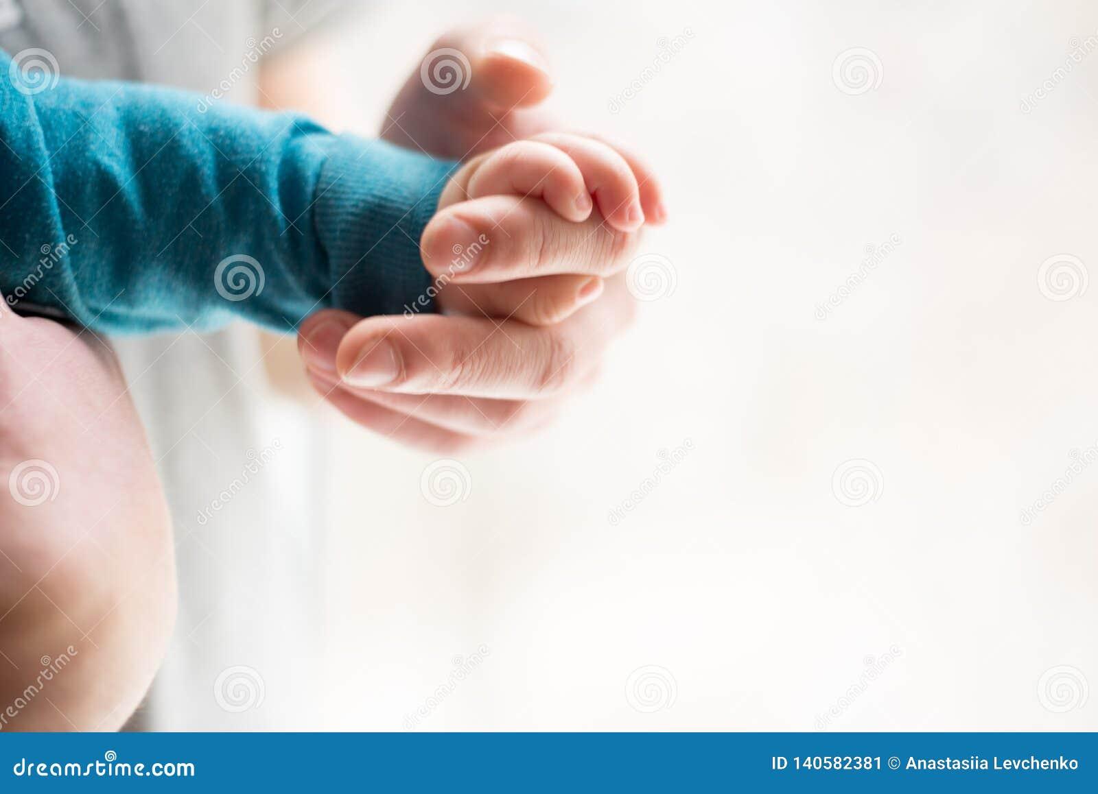 Hermanas que llevan a cabo las manos dé el bebé durmiente en la mano del primer del padre Manos en el fondo blanco