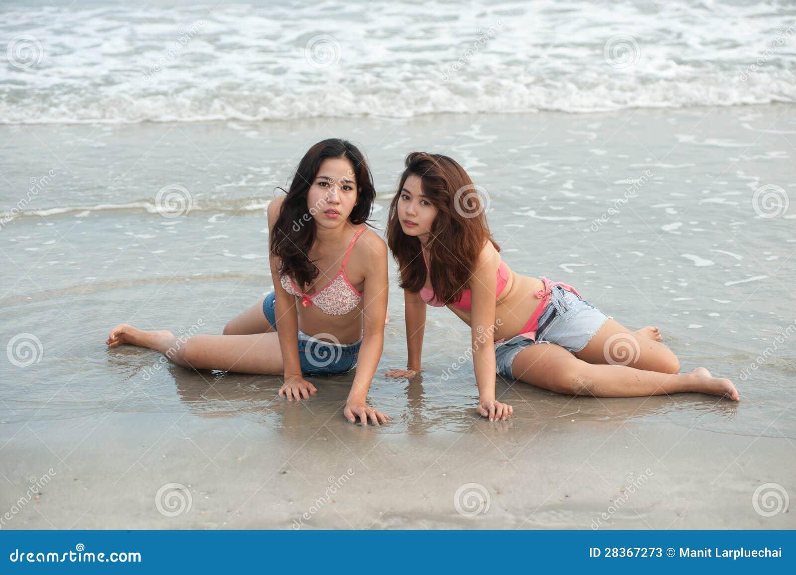 Hermane a la mujer bastante tailandesa que presenta en la playa.