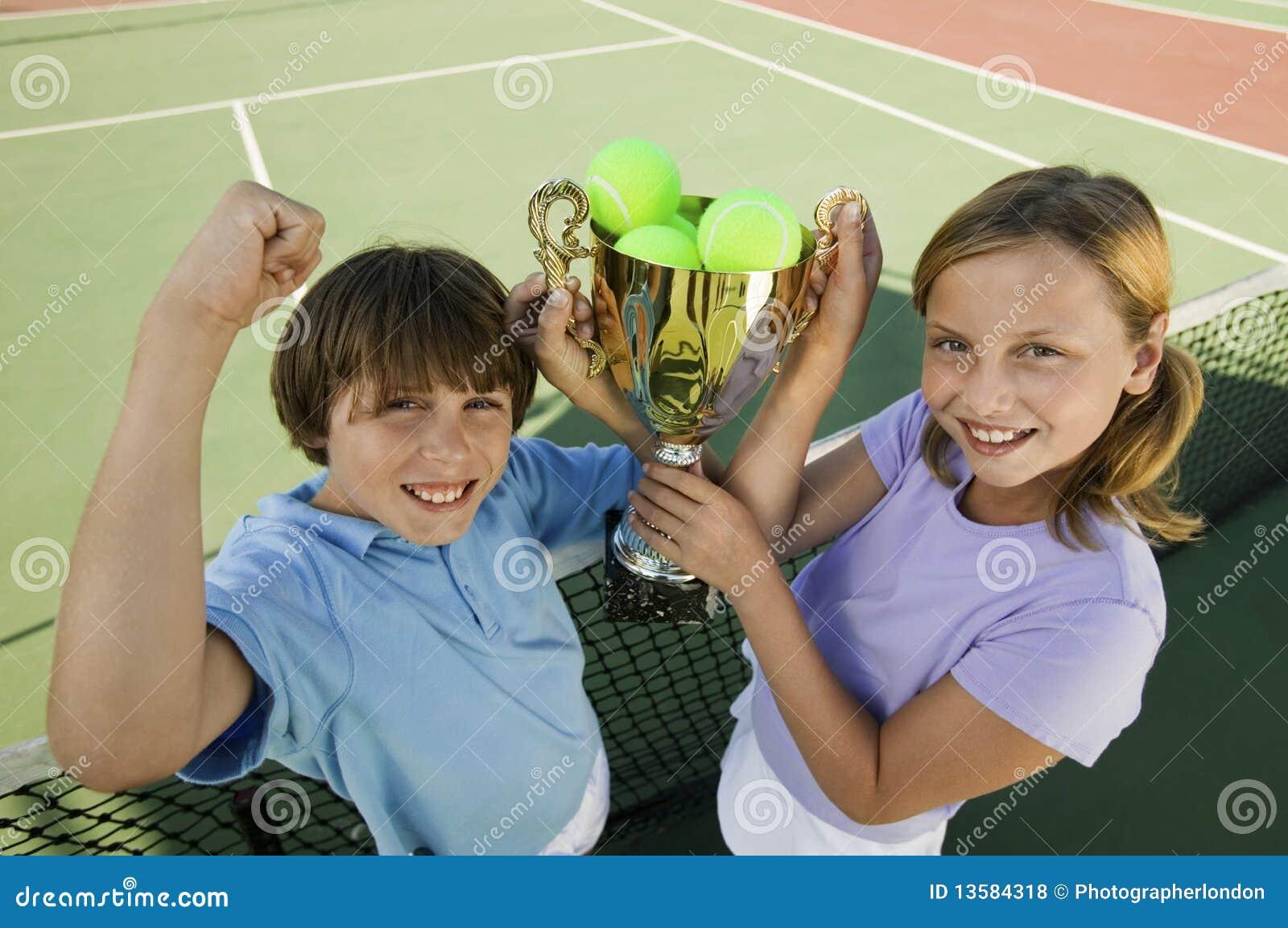 Hermano y hermana que soportan el trofeo del tenis