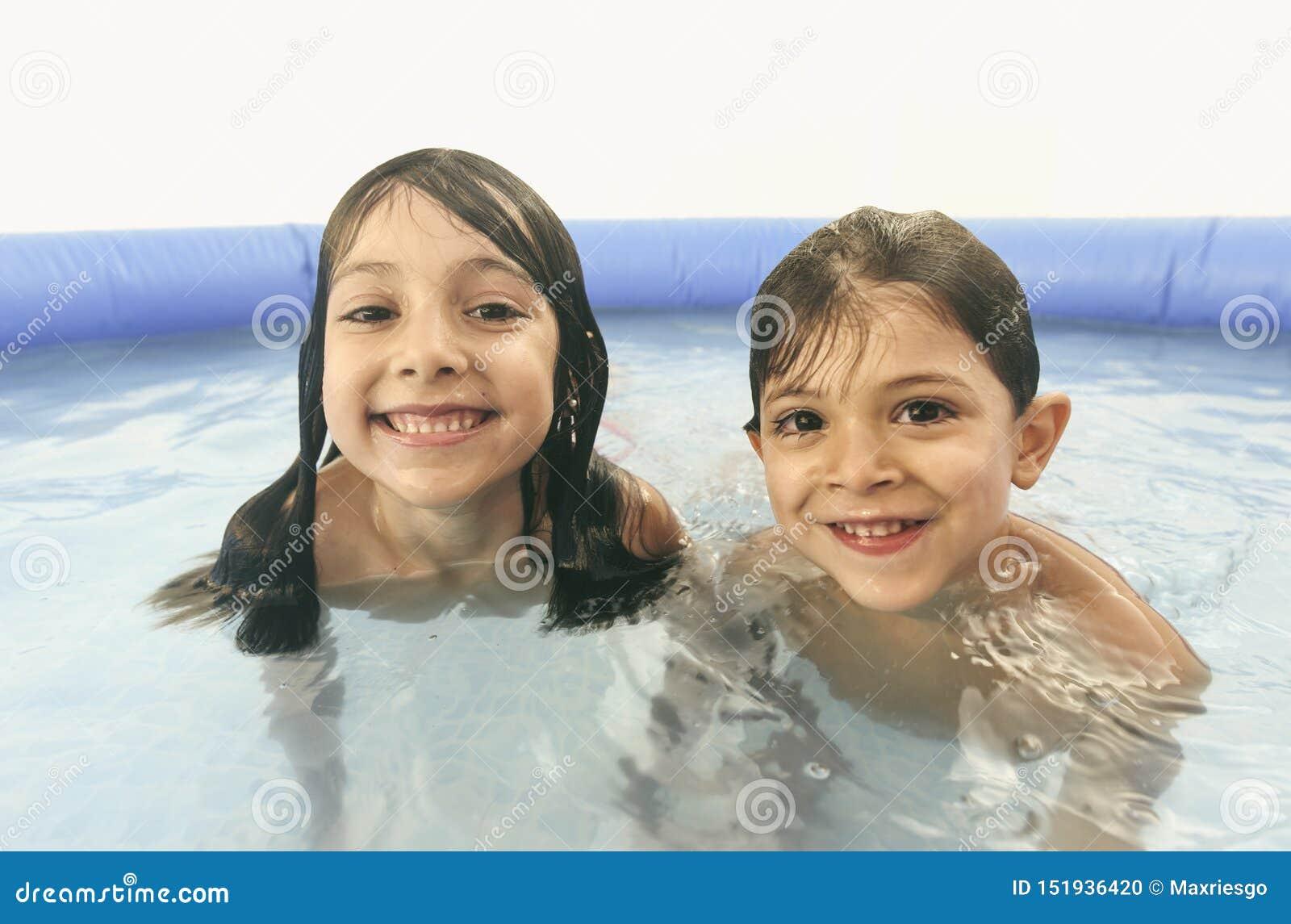 Hermanos que juegan en la piscina plástica que mira la cámara
