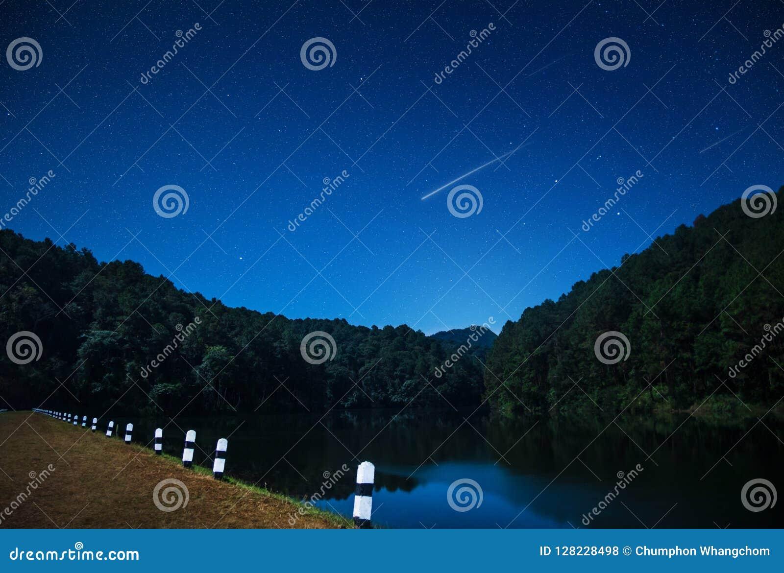 Hermosas vistas de la naturaleza en la noche con la estrella fugaz en la presa septentrional de Tailandia