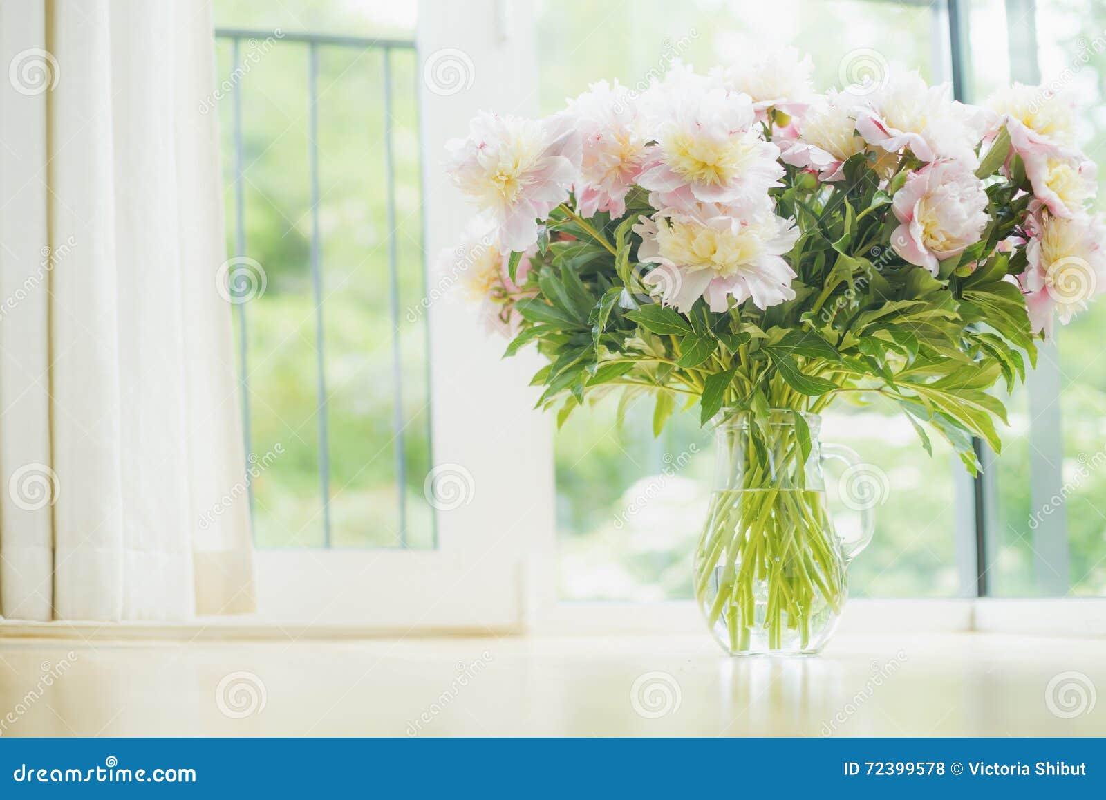 Hermosos grandes palidecen - el ramo rosado de las peonías en el florero de cristal sobre fondo de la ventana Decoración casera l