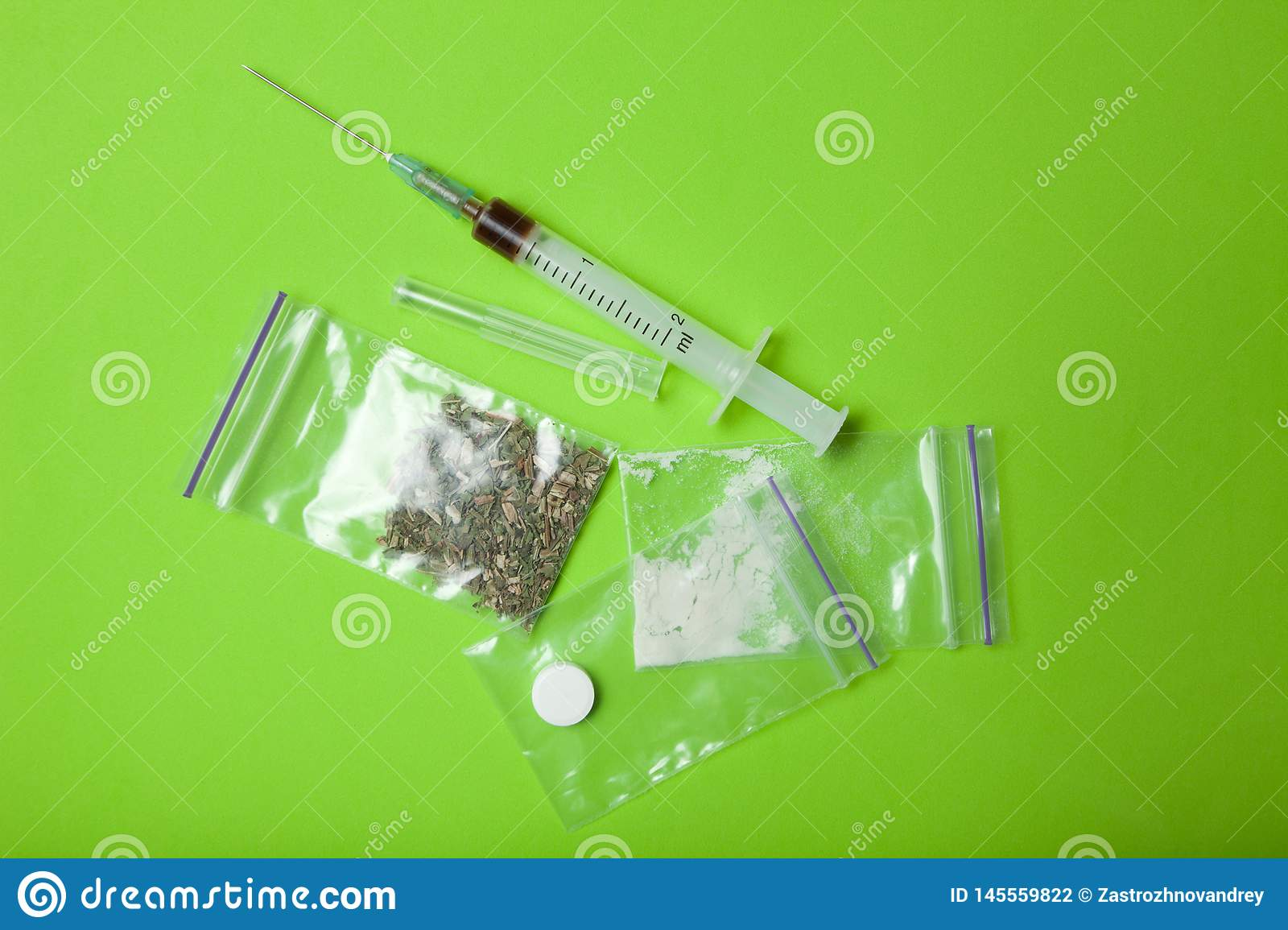 Heroin, cocaine, marijuana and ecstasy on a green background