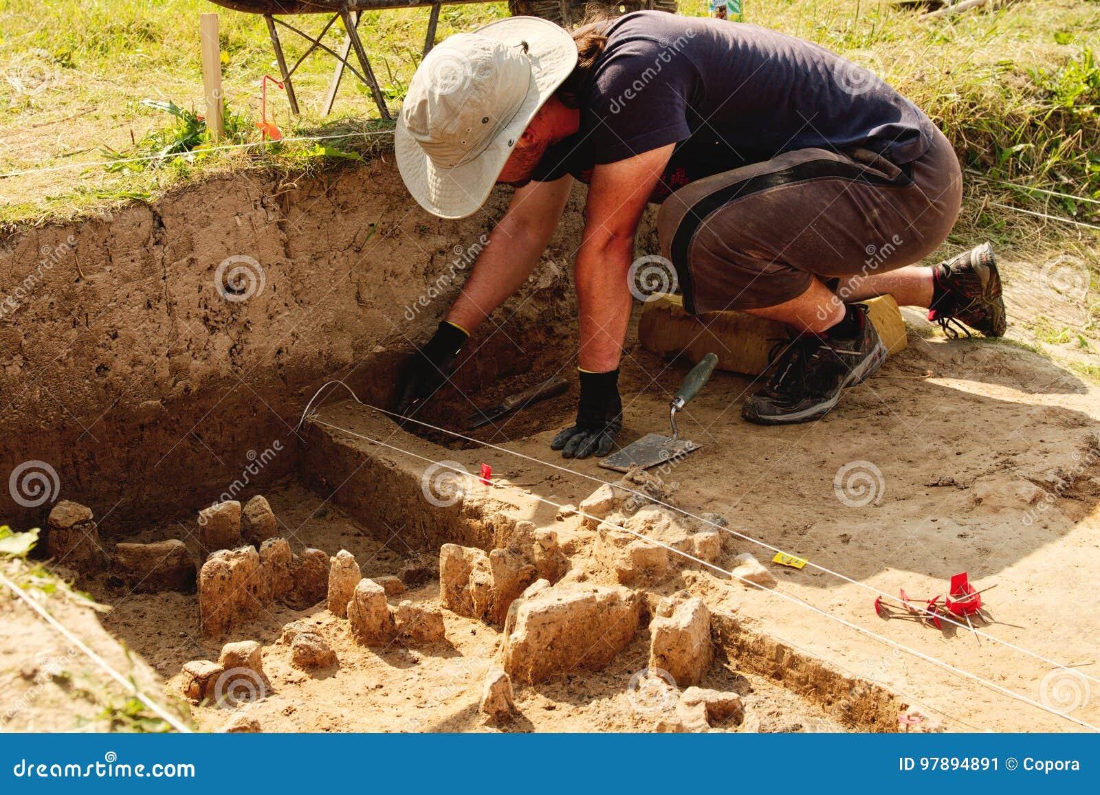 Herramientas arqueológicas, arqueólogo que trabaja en sitio, mano y herramienta