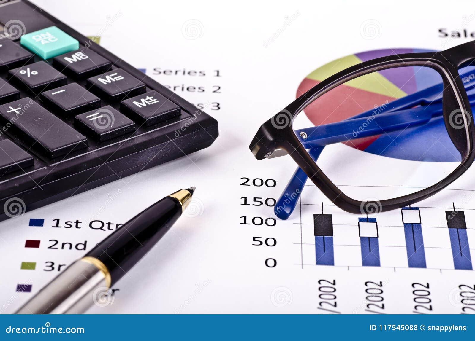 Herramientas, calculadora, pluma y gafas financieras sobre un informe