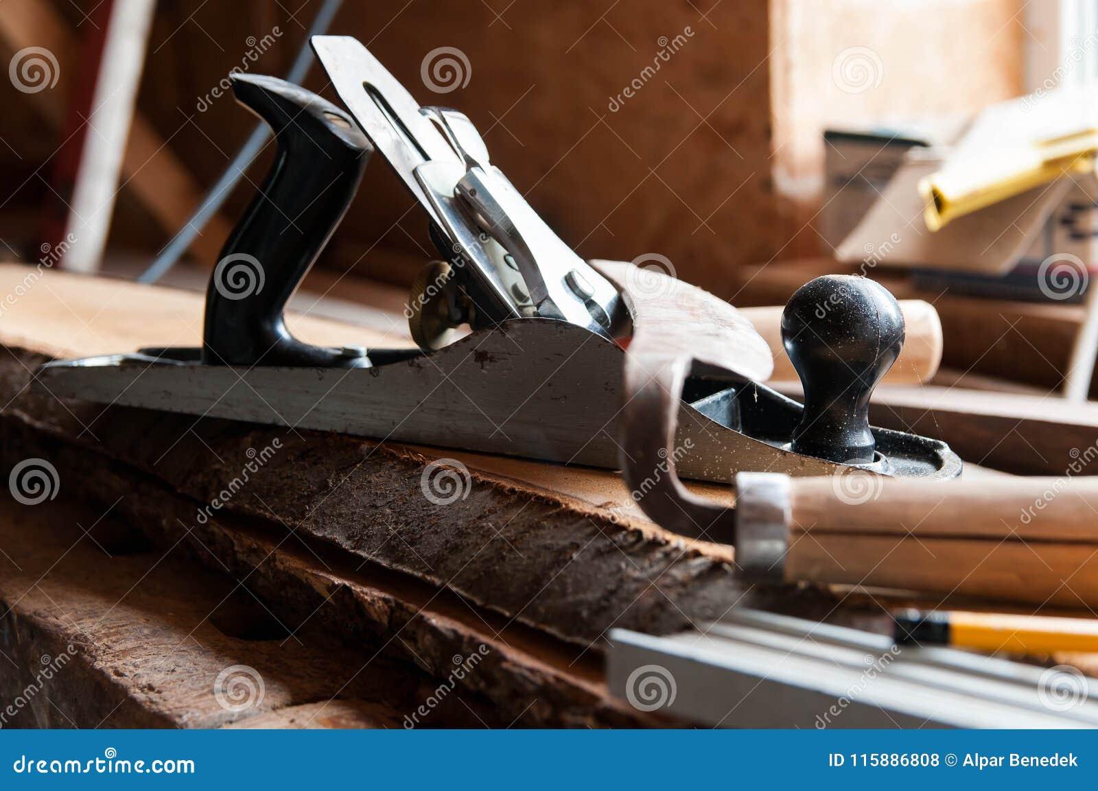 Herramientas de la carpintería en los tableros de madera, foco en el avión