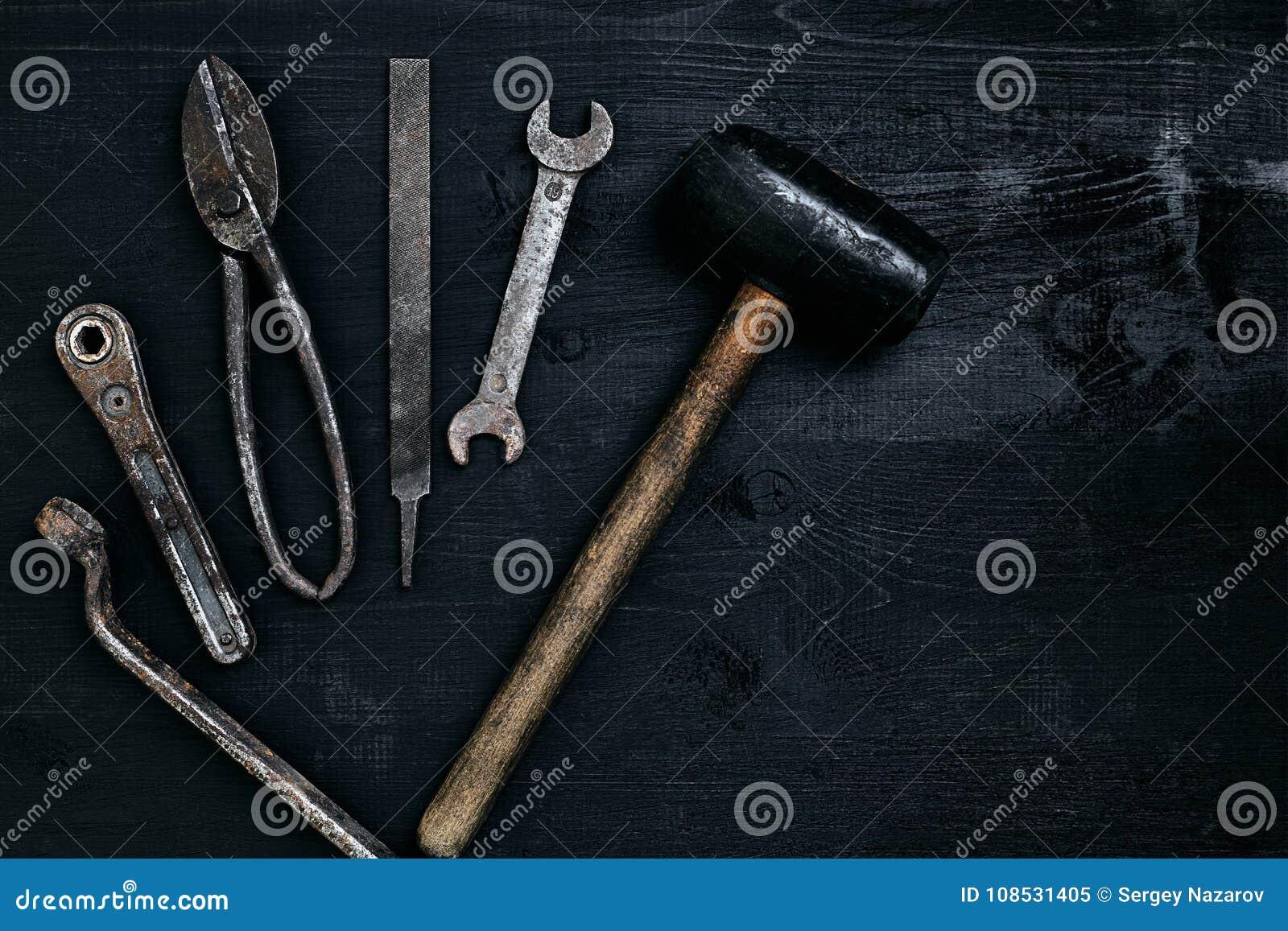 Herramientas viejas, oxidadas que mienten en una tabla de madera negra El martillo, cincel, metal scissors, llave