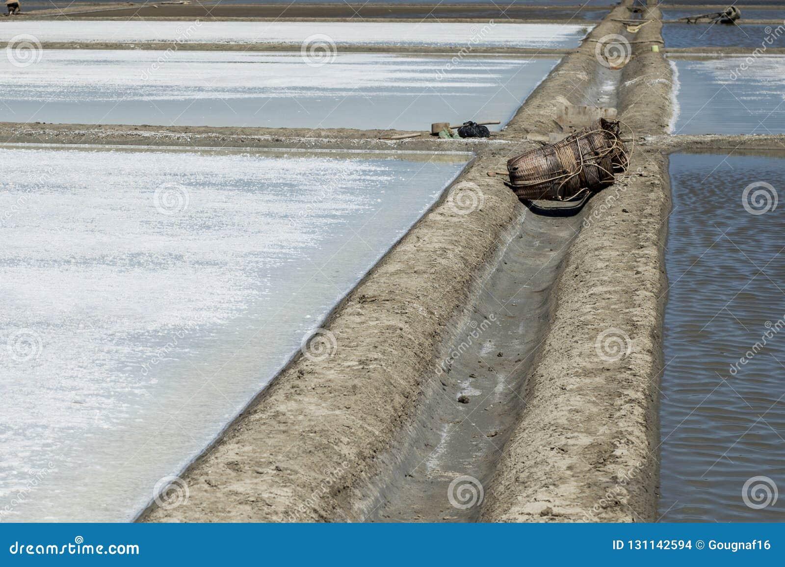 Herramientas y bolsos de mimbre tejidos dejados en los saladares vacíos por la tarde en Gio de la poder, Vietnam