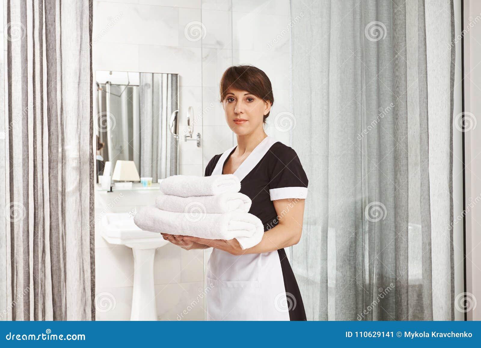 Herren ska jag sätta extra handdukar i badrum Ståenden av kvinnan i enhetligt anseende för hembiträde med vita hotellhanddukar ne