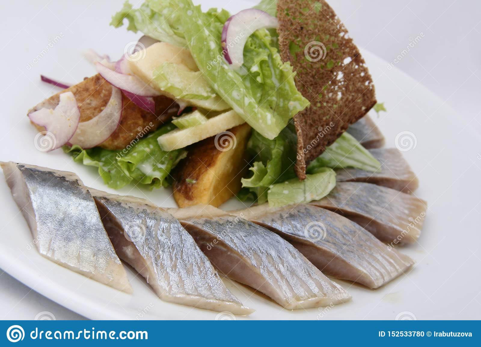 Herring fish with potatoes slices, greens, red onion and rye bread