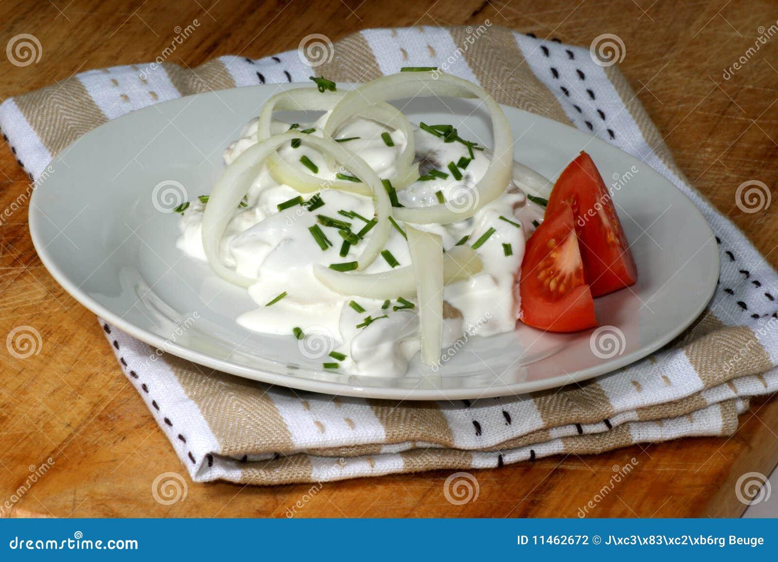 herring in yogurt sauce on a white plate