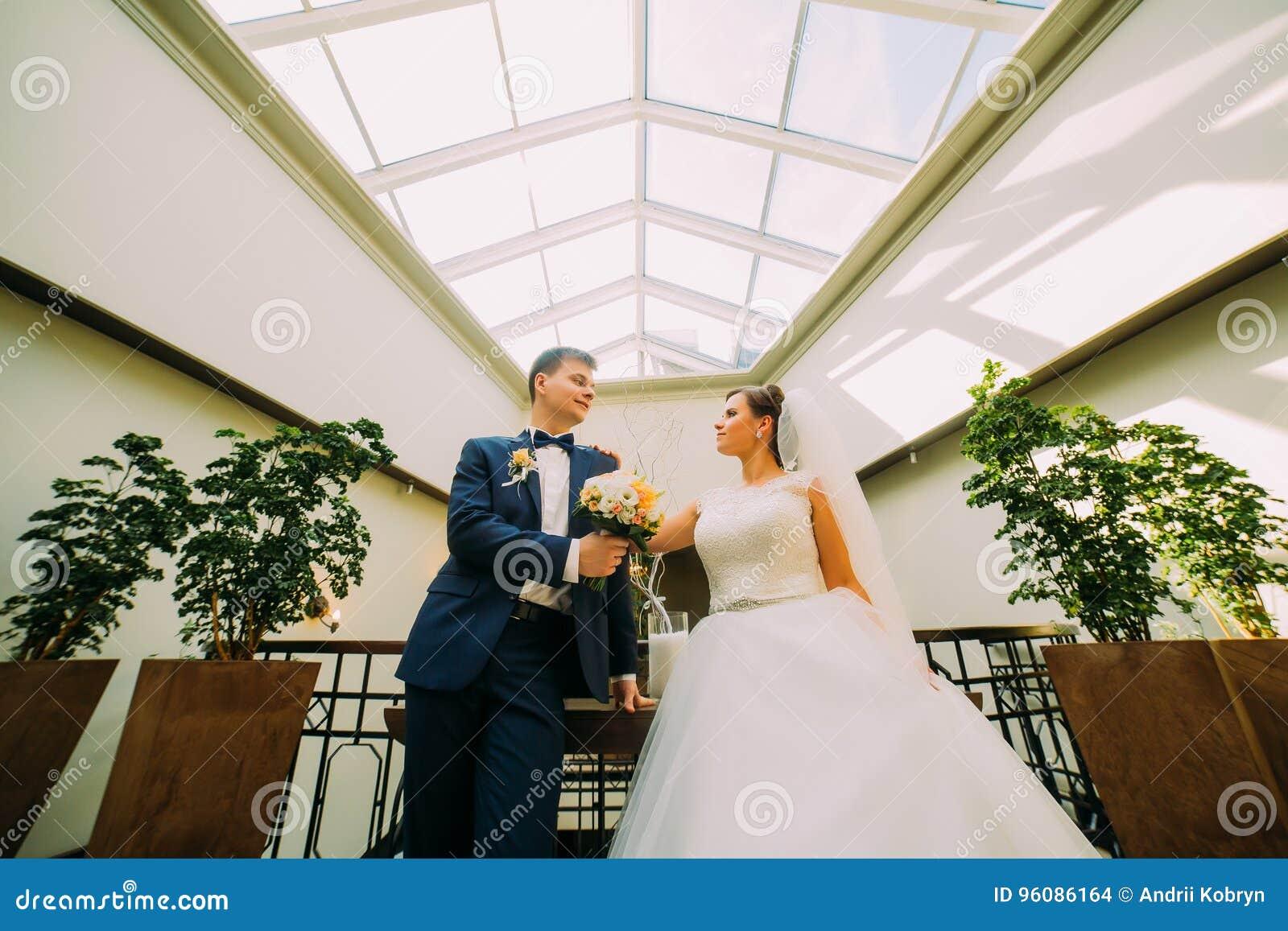 Herrliche Braut und eleganter Bräutigam, die im modernen Hintergrund aufwirft Ansicht von unterhalb