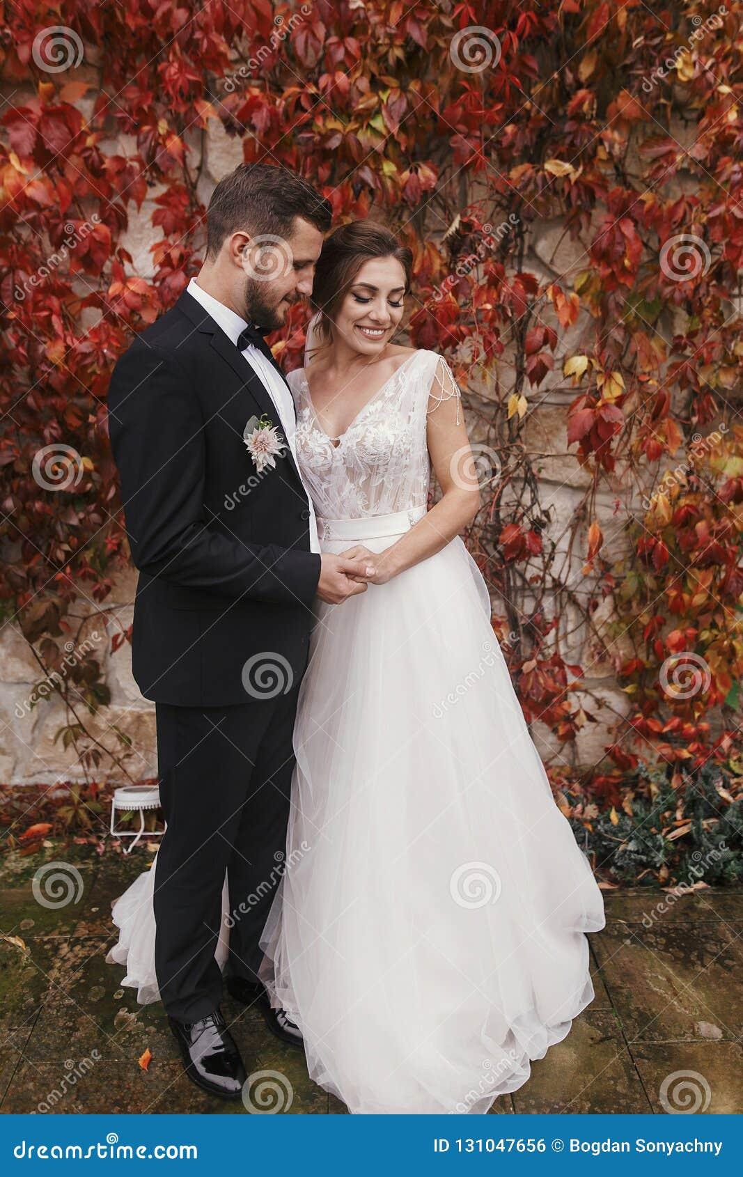 Herrliche Braut und stilvoller Bräutigam, die leicht an w umarmt und lächelt