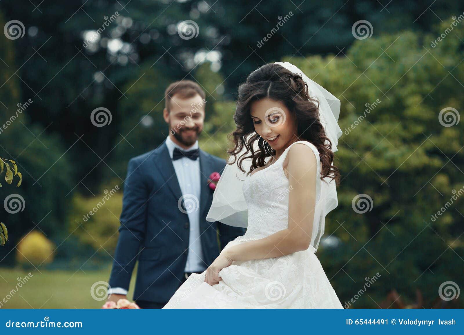 Herrliche Brunettebraut im eleganten Kleid, das im Park mit aufwirft