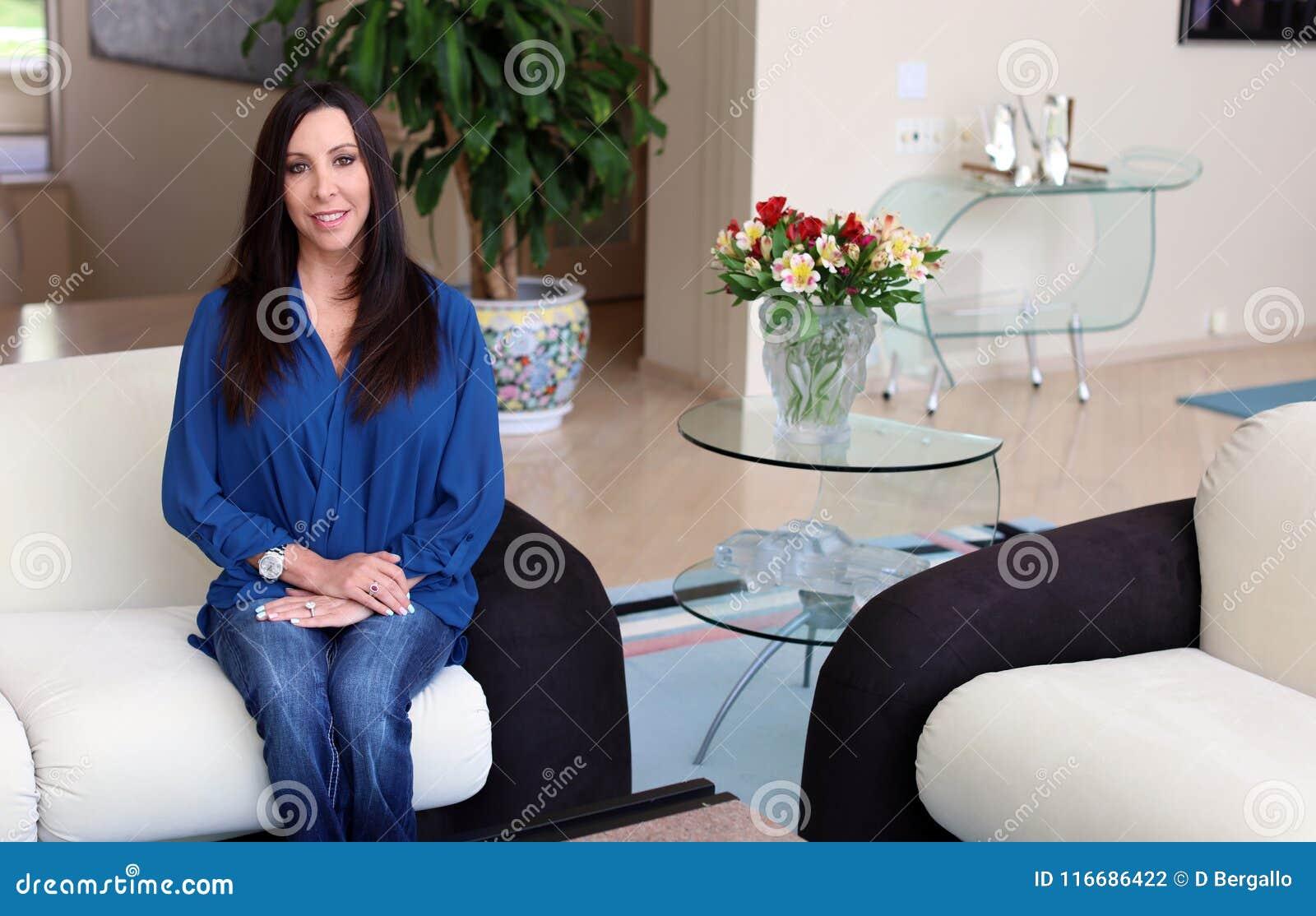 Herrliche Frau des dunklen Haares, die mit schönem blauem Hemd, Berufspsychologe in einem Art- DecoRaum lächelt