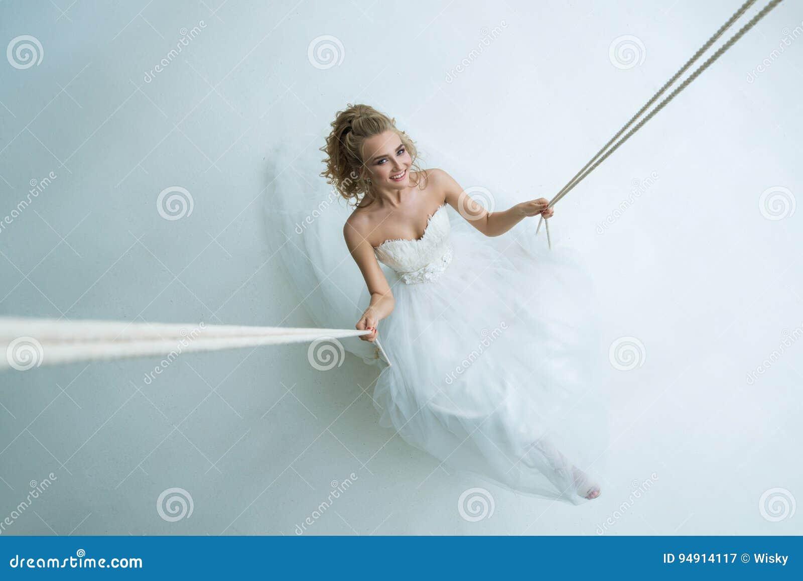 Herrliche junge Braut auf Schwingen im Studio