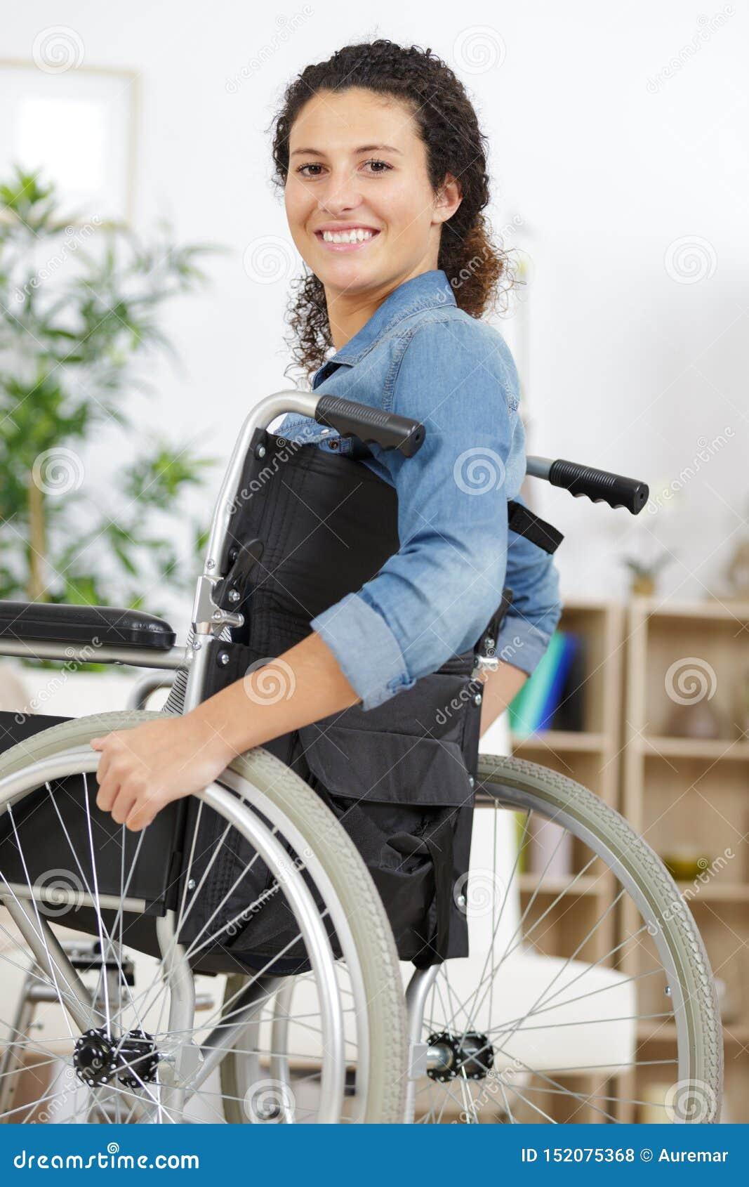 Herrliche junge Frau auf dem Rollstuhl, der sich zu Hause entspannt