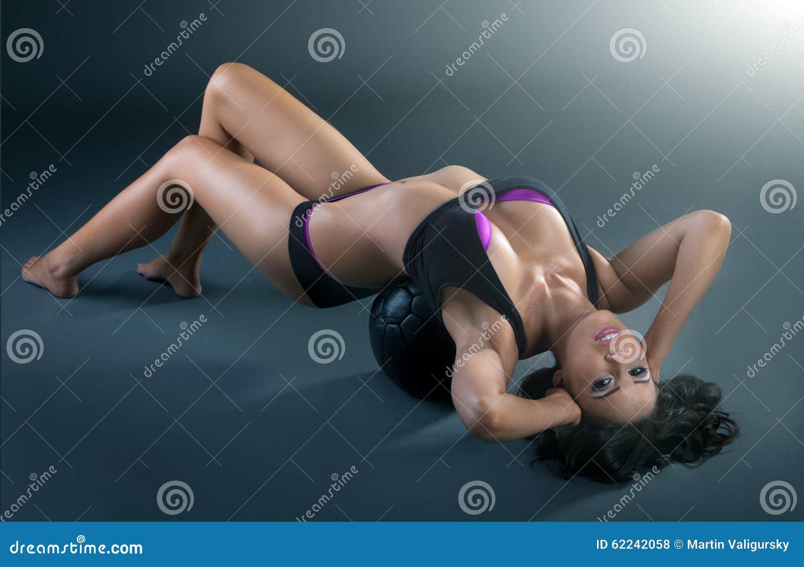 Herrliche junge Frau, die auf den Sitzball, Training tuend legt