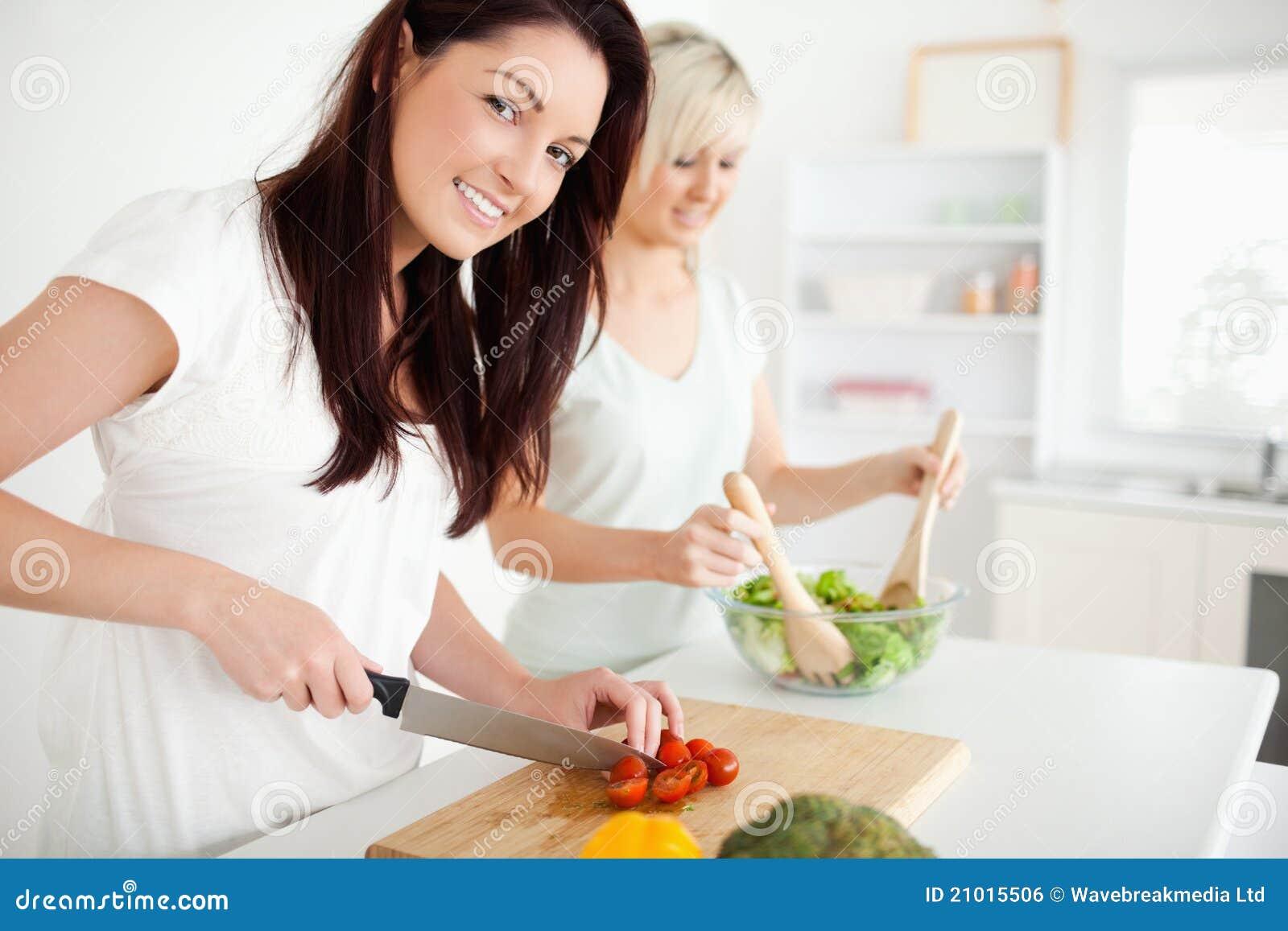 Herrliche junge Frauen, die Abendessen vorbereiten